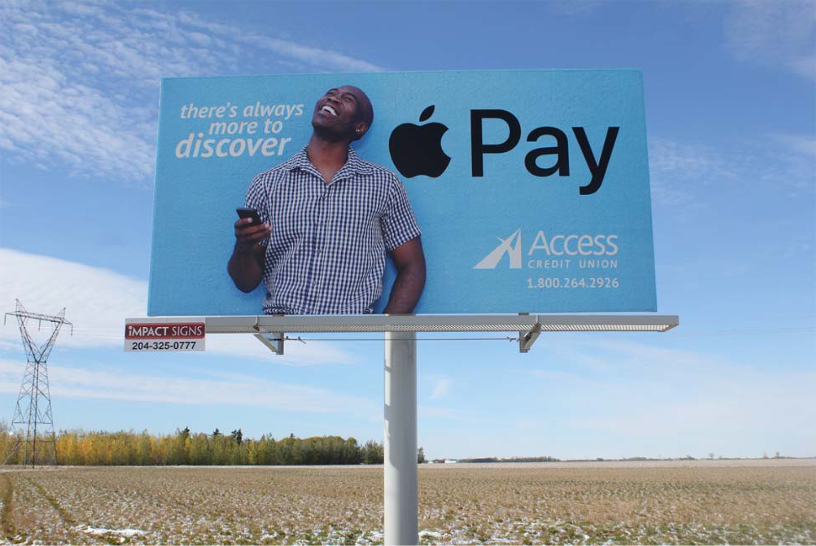 Billboard with a young African American man in a checked short-sleeved shirt smiling, holding a cell phone.