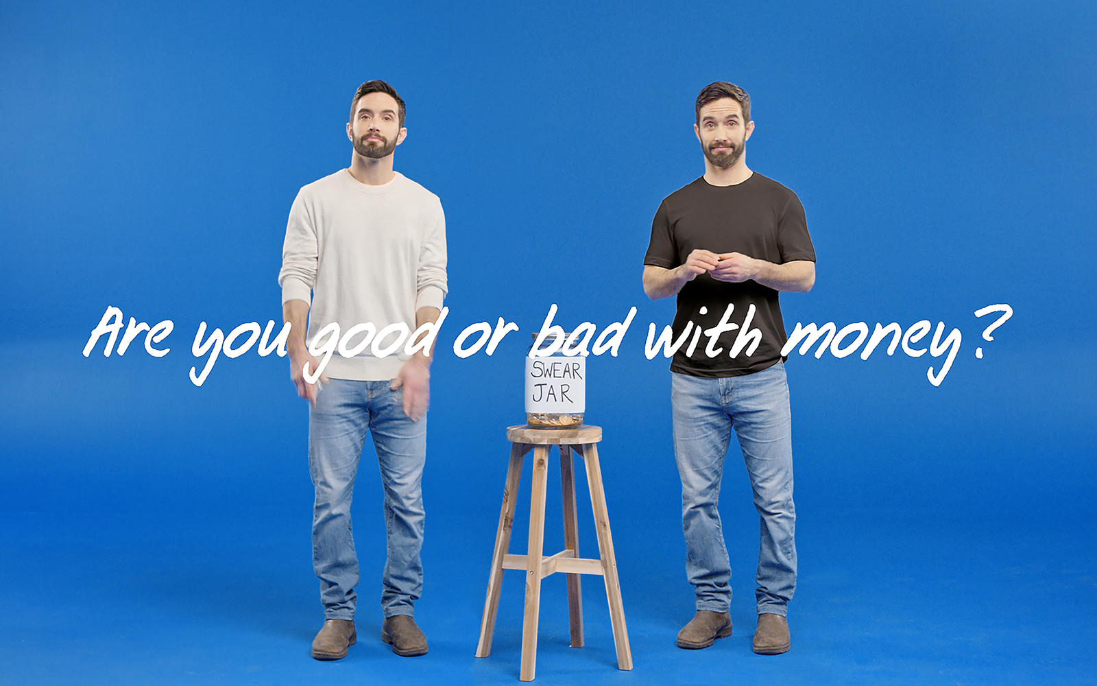 A young bearded man wearing a white sweater standing with the same bearded man wearing a black sweater, with a stool in between them. On the stool is a swear jar.