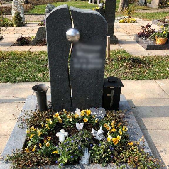 würdiger Urnengrabstein mit Kugel und Beschriftung