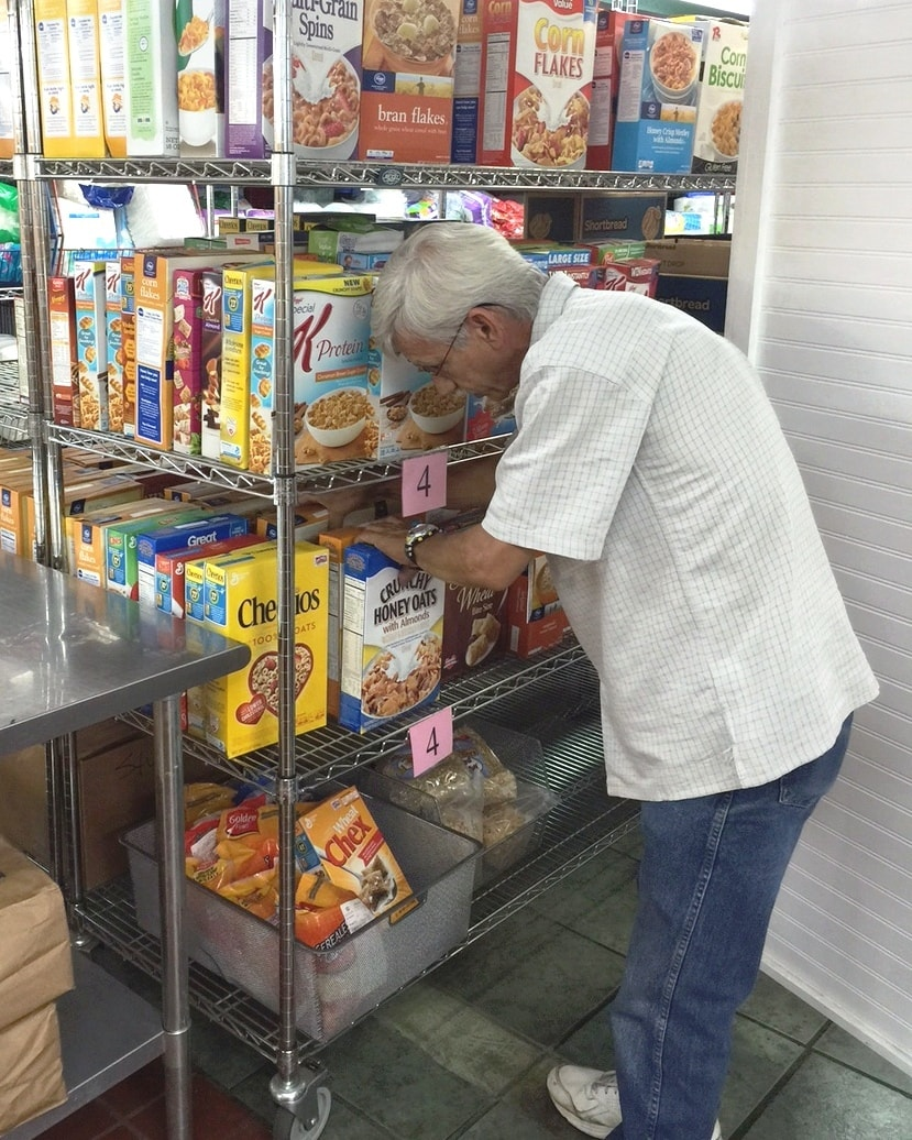 A volunteer helps stock shelves in our Food Pantry