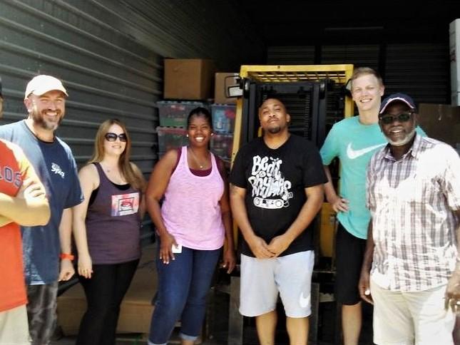 Volunteers help move donated goods
