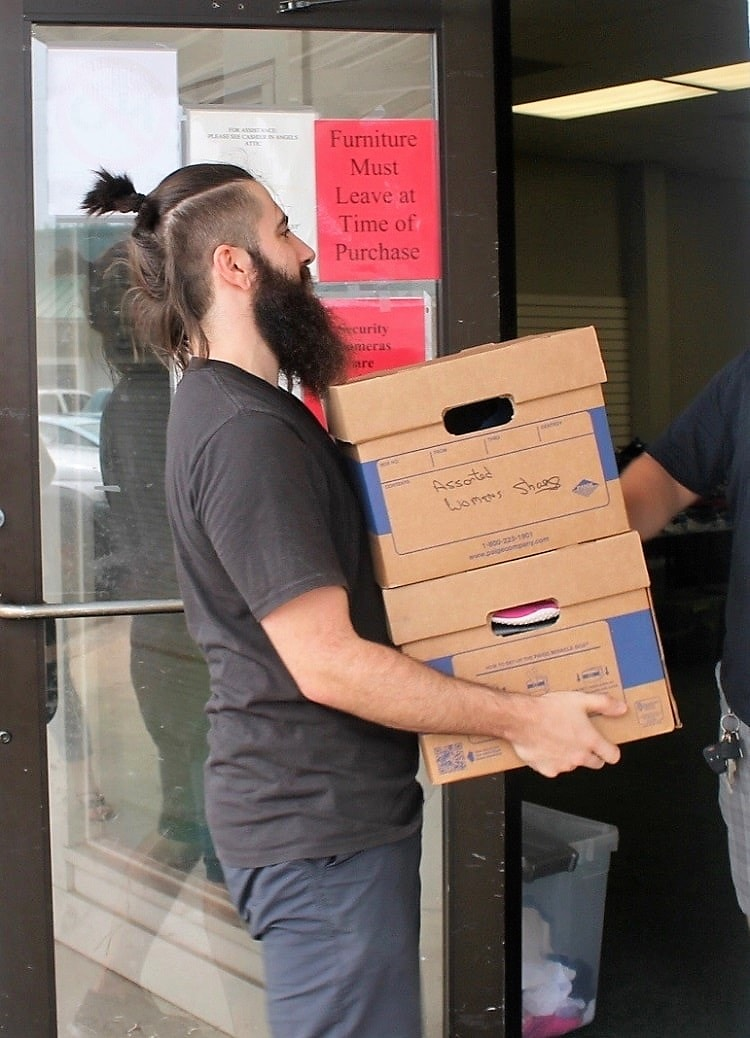 A volunteer moving donated goods at CAM