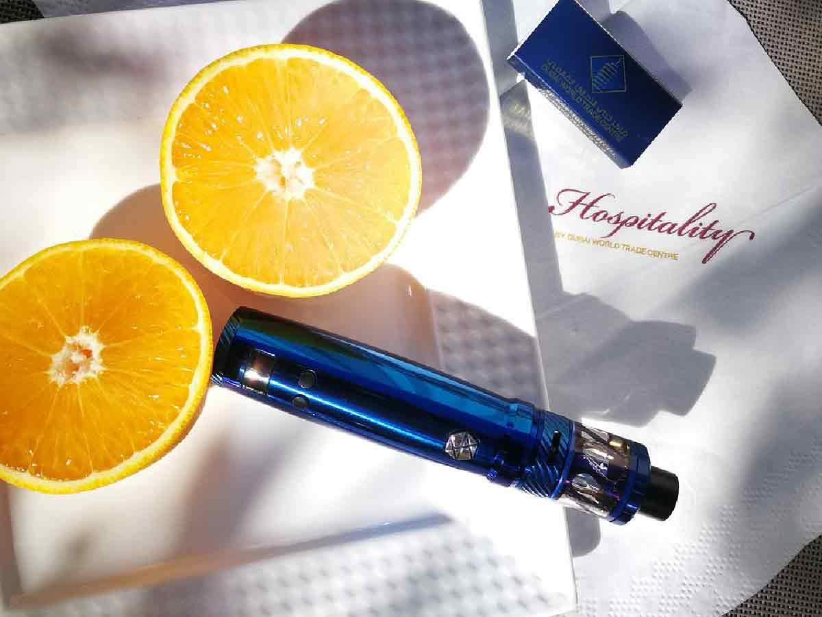 una sigaretta elettronica blu su una scrivania con arance