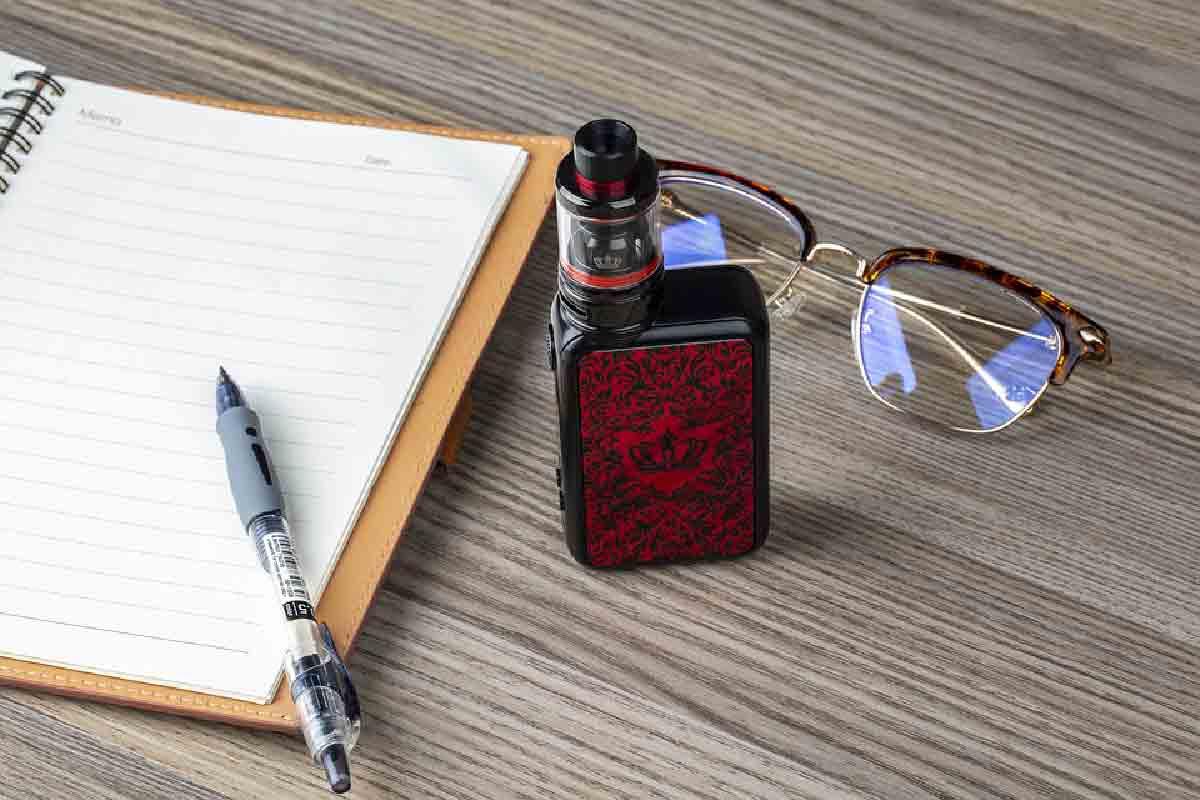 sigaretta elettronica su scrivania con occhiali e agenda