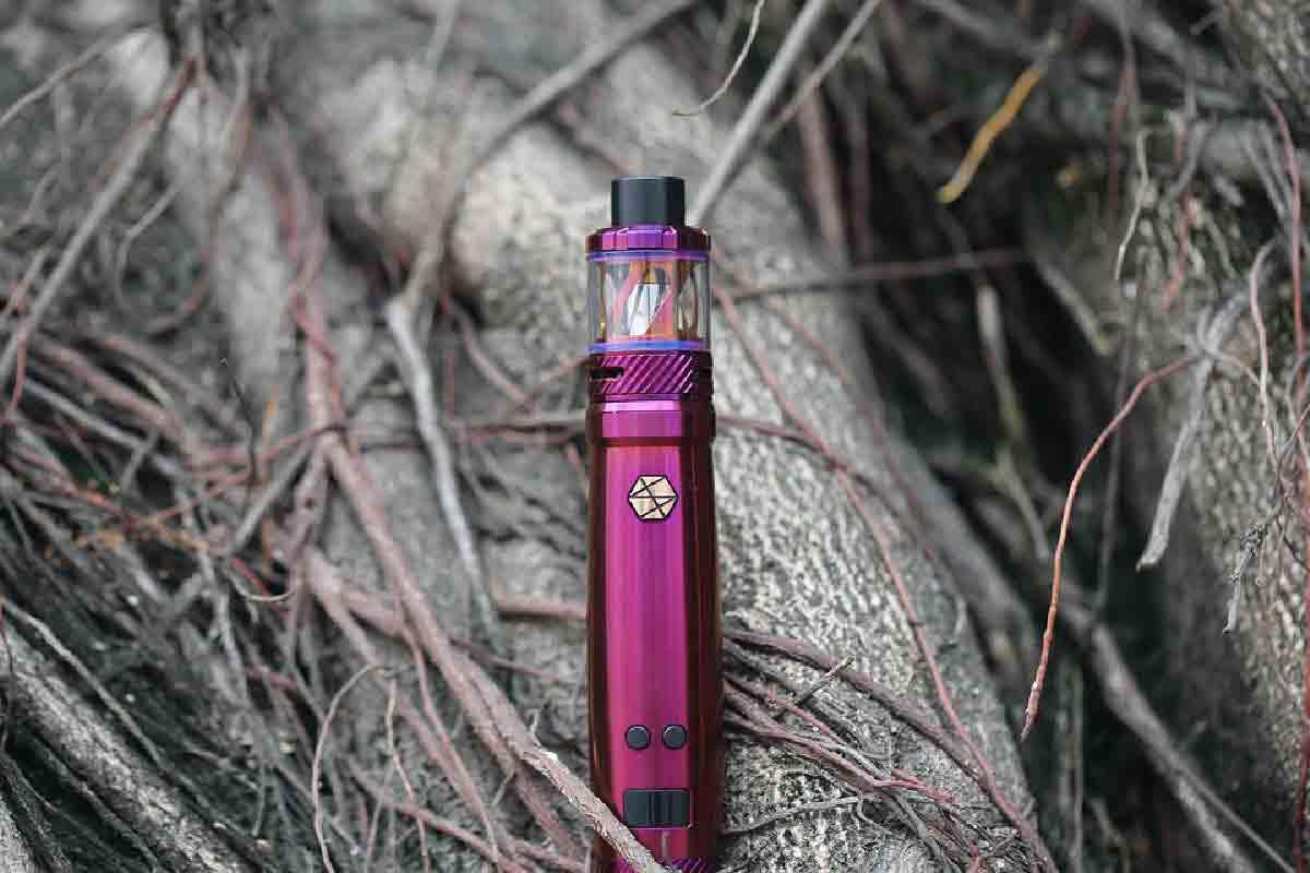 una sigaretta elettronica viola ripresa in primo piano sullo sfondo di arbusti