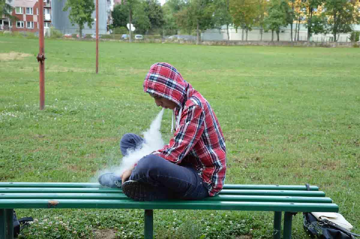un ragazzo viene ripreso mentre svapa su una panchina