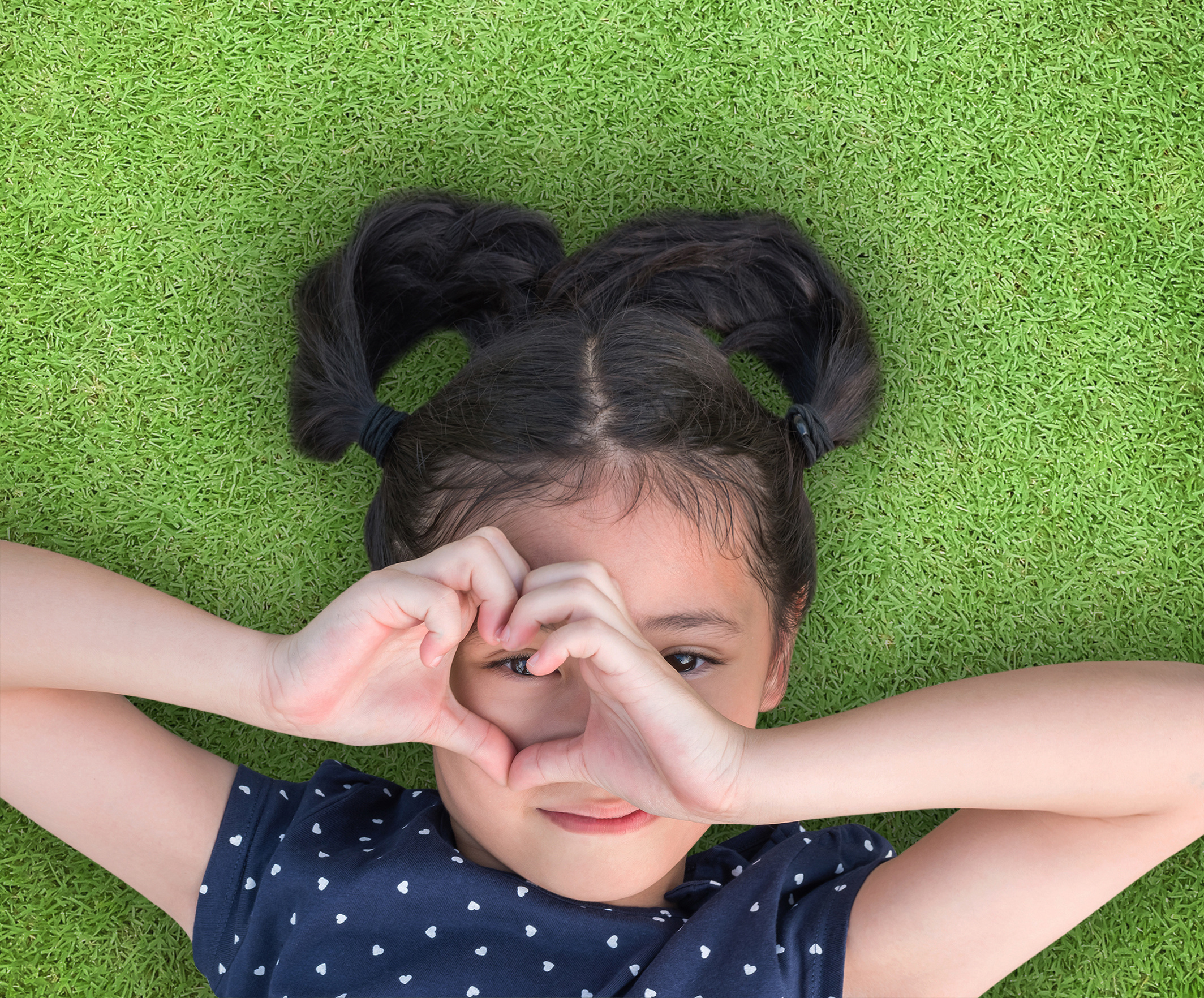 Young girl with hand in a heart shape around eye