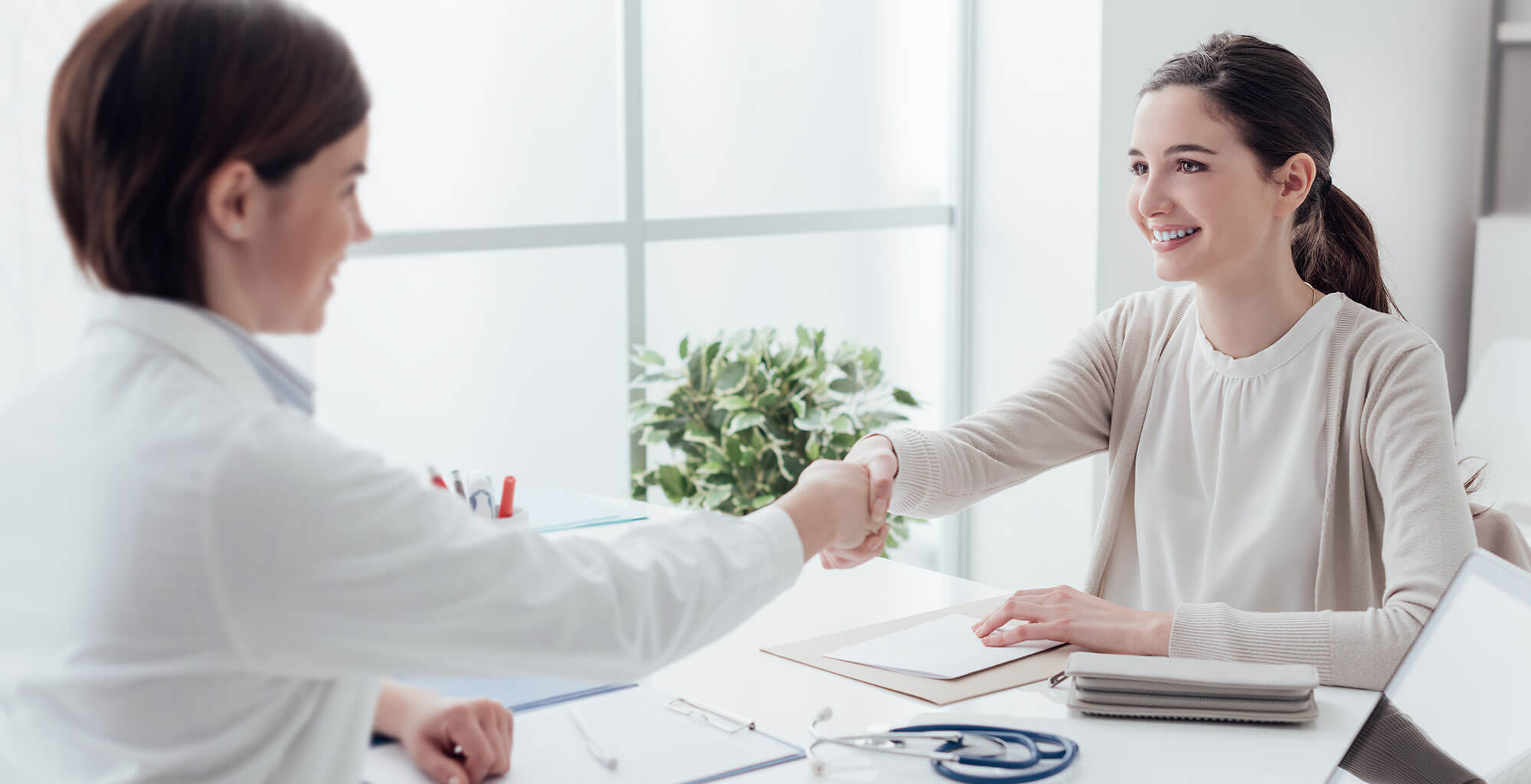 Happy patient shaking hands with direct primary care doctor in Denver