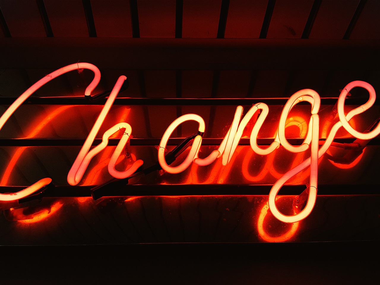 """A neon sign with the """"change"""" in red"""