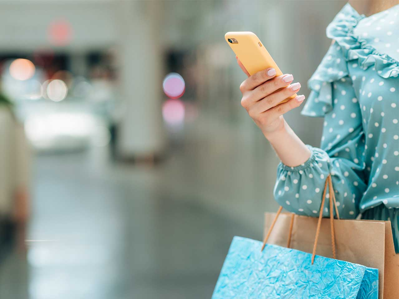 woman using her phone while holding a shopping bag