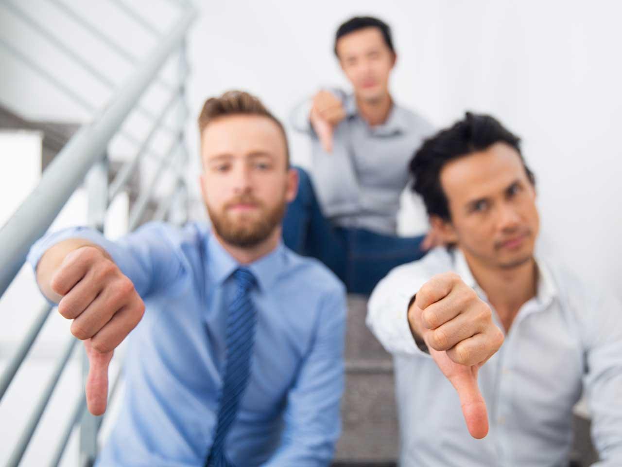three men doing a thumbs down