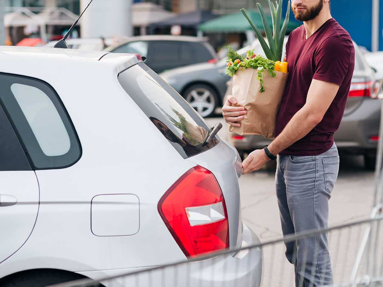 man putting items in his car's trunk