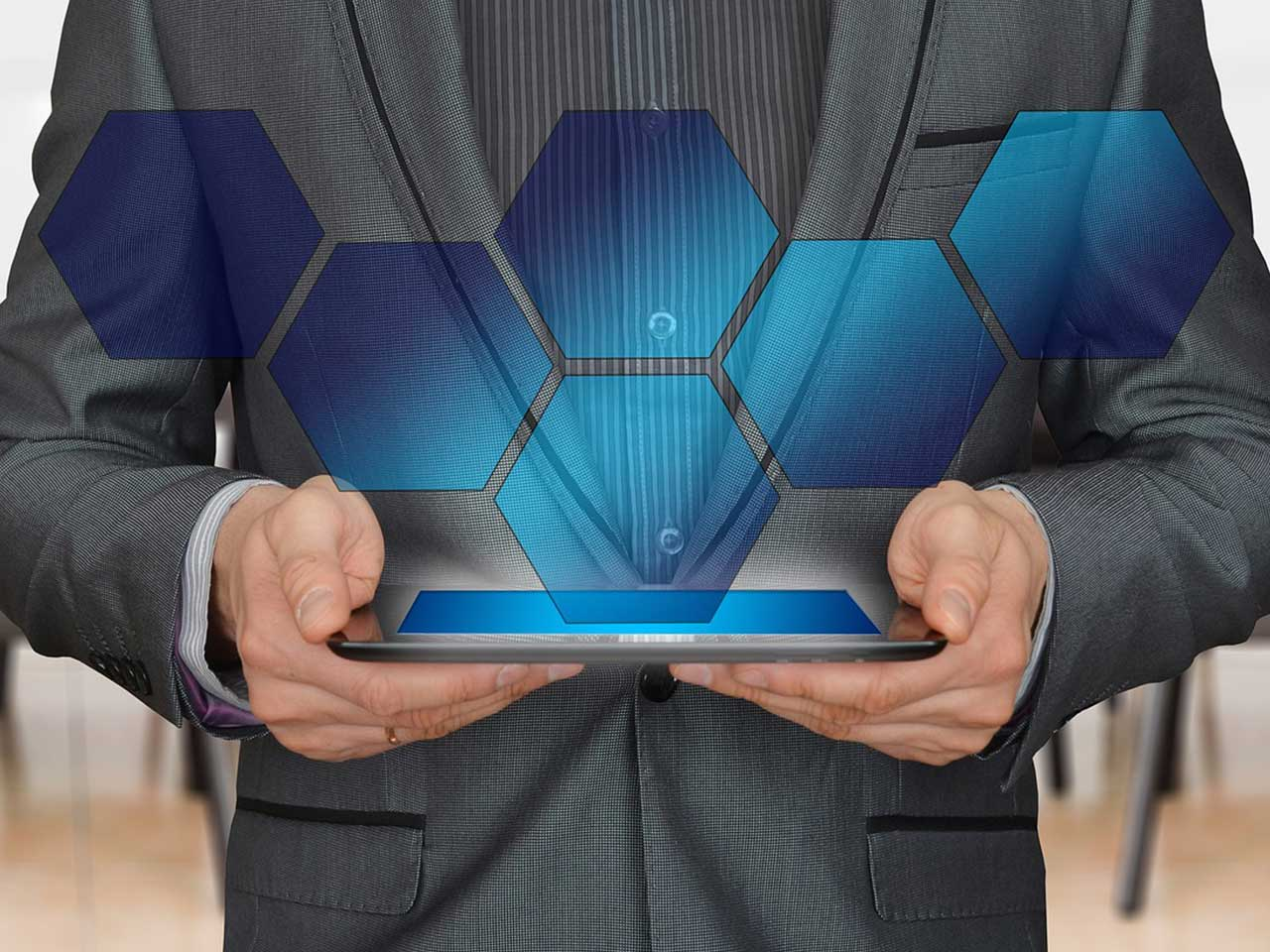 man holding an iPad showing a hexagon hologram
