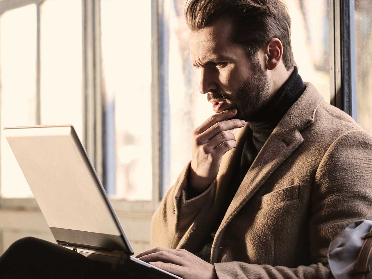 Man looking confused looking at his laptop