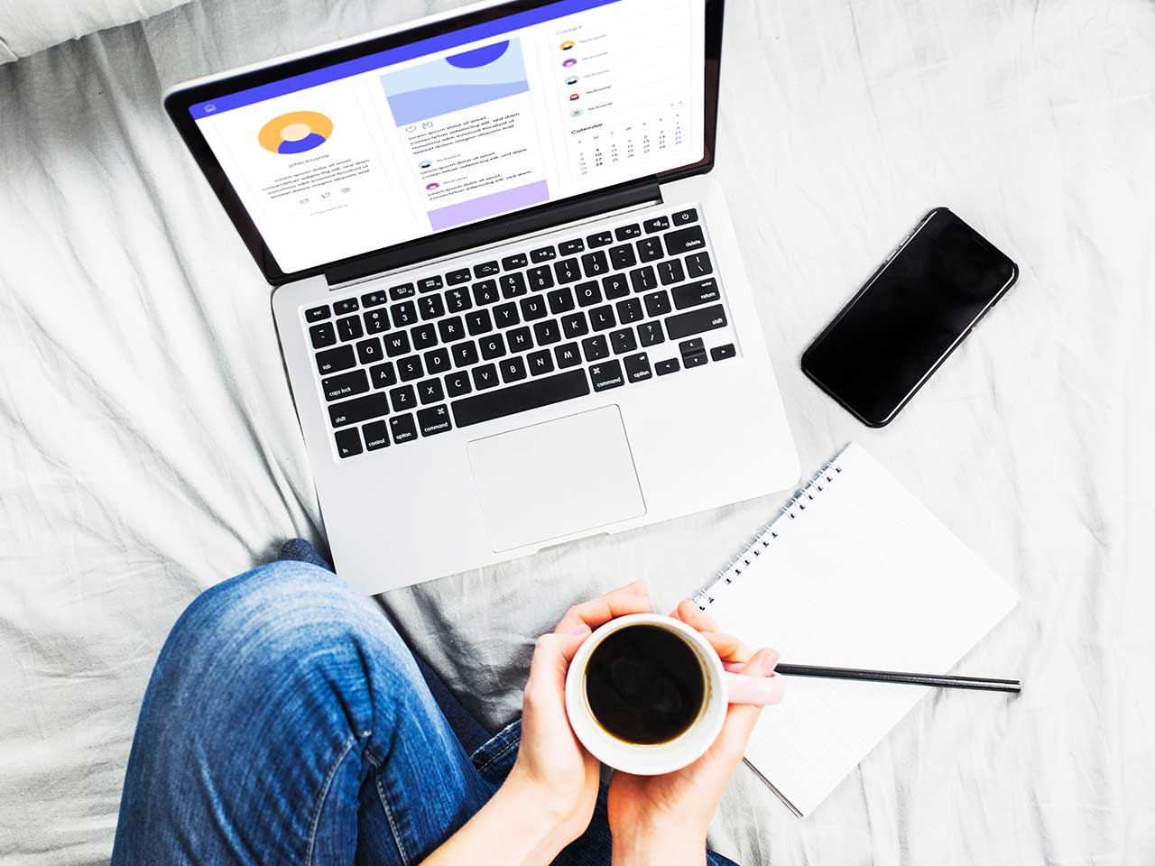 Person doing work on bed with coffee cup and laptop