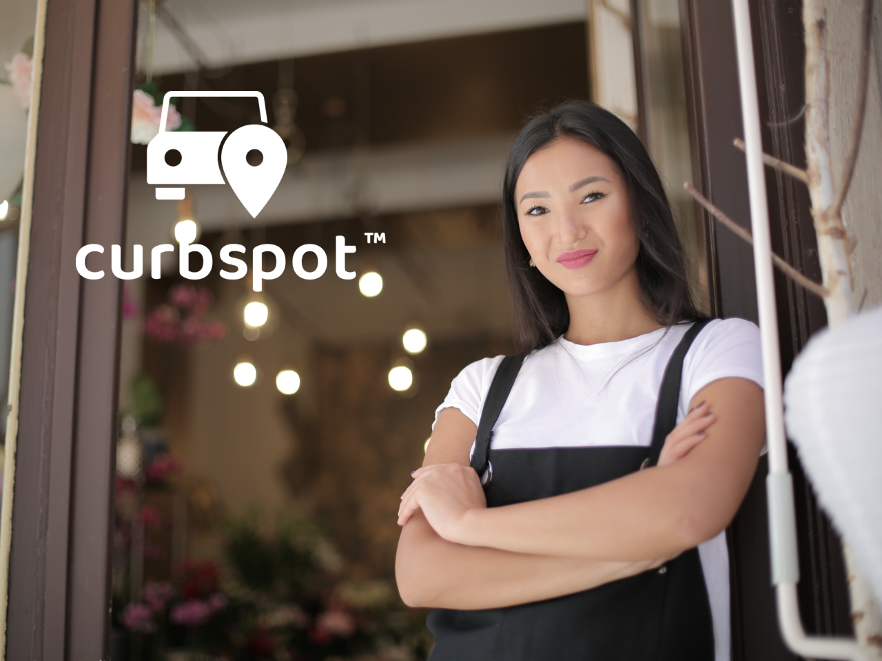 Curbspot: woman smiling in front of store with arms crossed