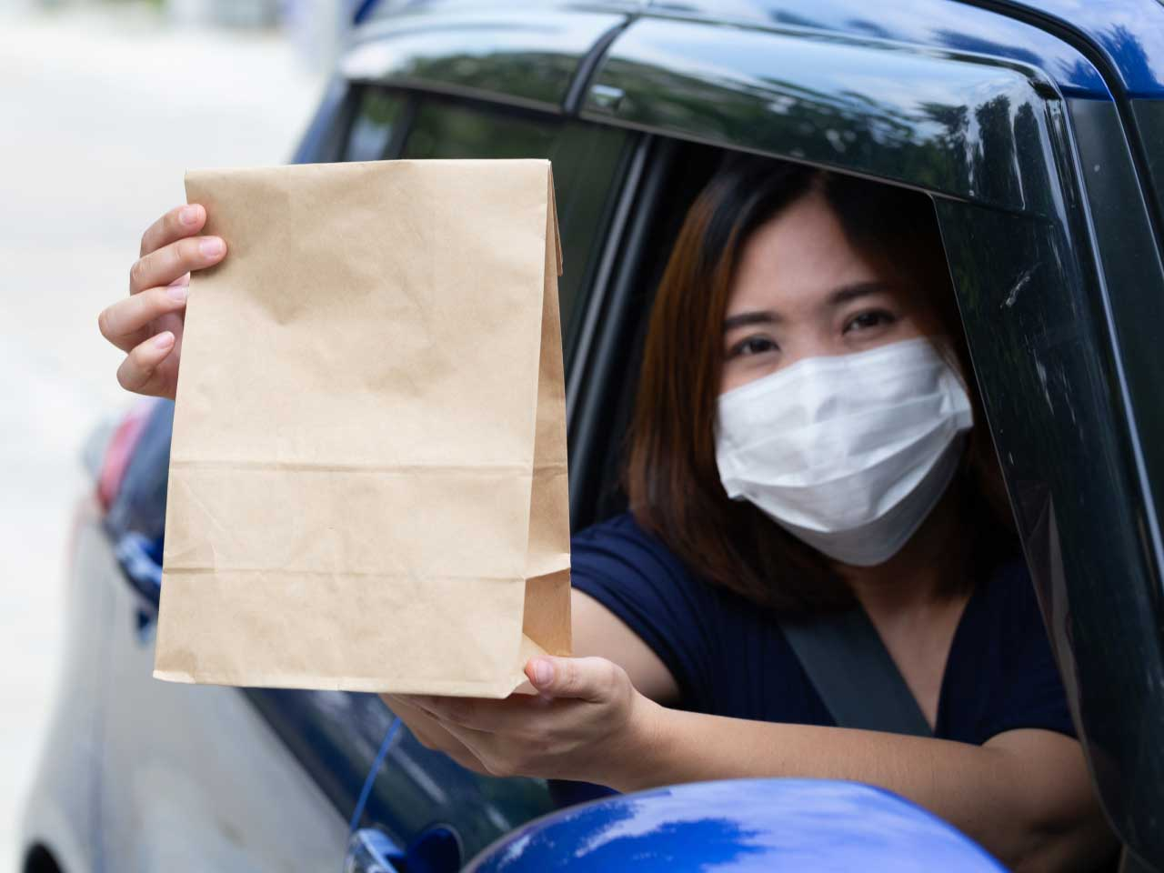 asian woman wearing mask holding paper bag
