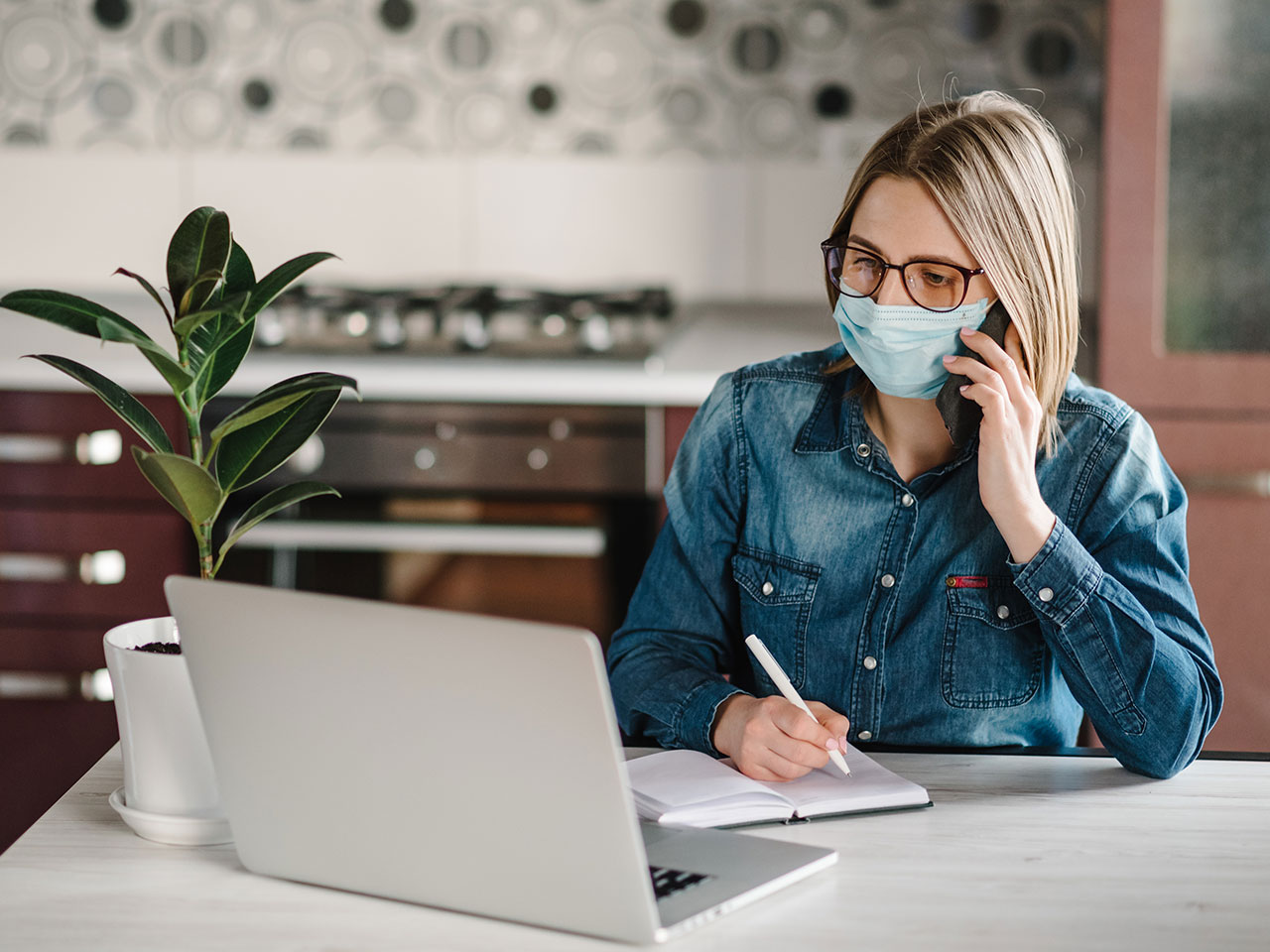 woman wearing mask working at home