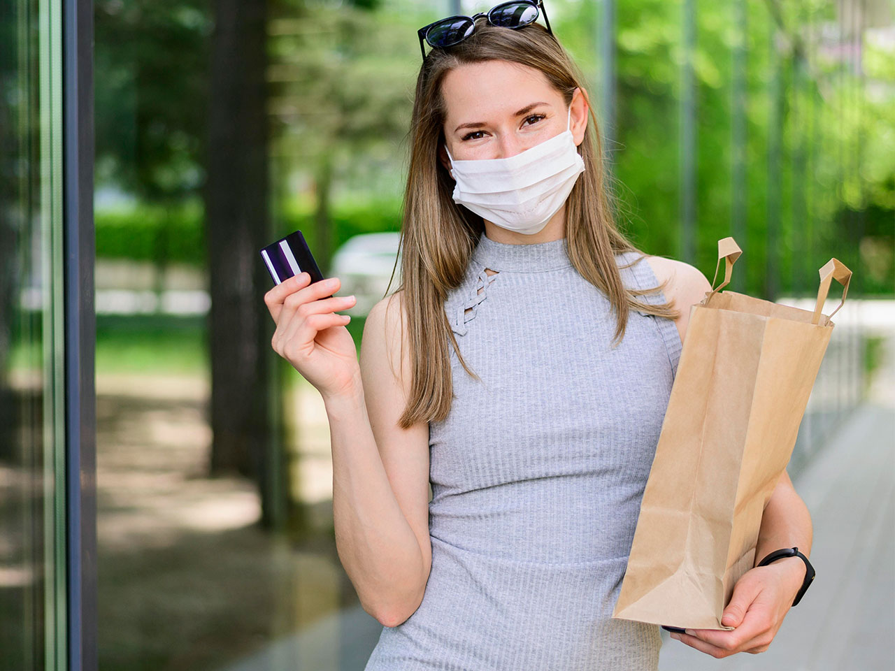 girl with face mask holding a paper bag and a credit card