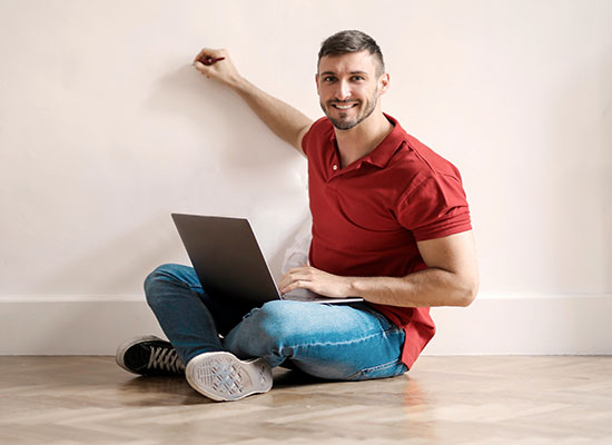 man with his laptop pointing a pen in the wall