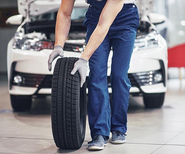 mechanic-holding-tire-tire-repair-garage-replacement