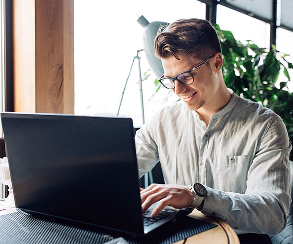 attractive-businessman-eyeglasses-working-laptop-typing-spending-time-cafe