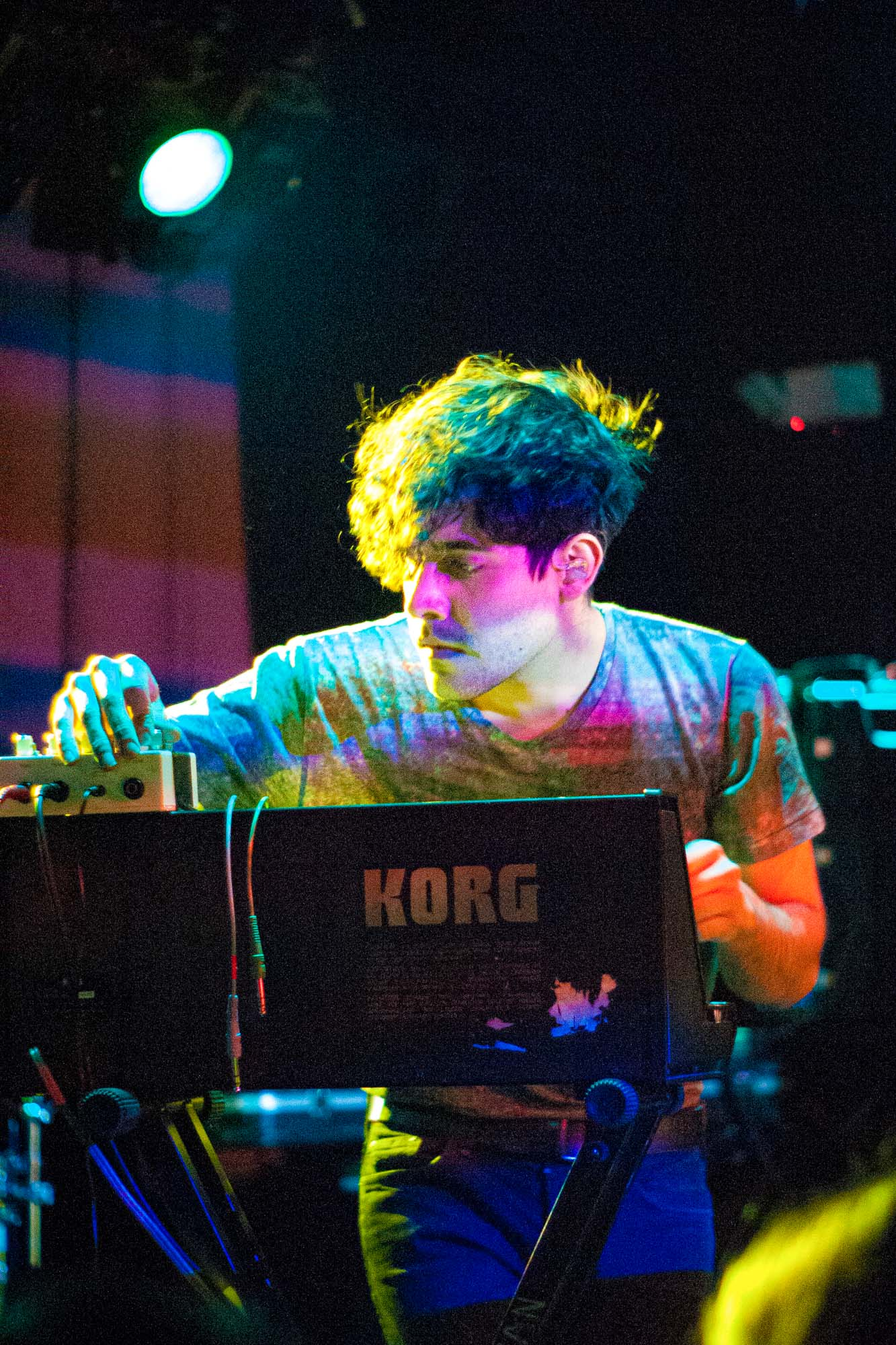 a musician plays a synthesizer at a rock club