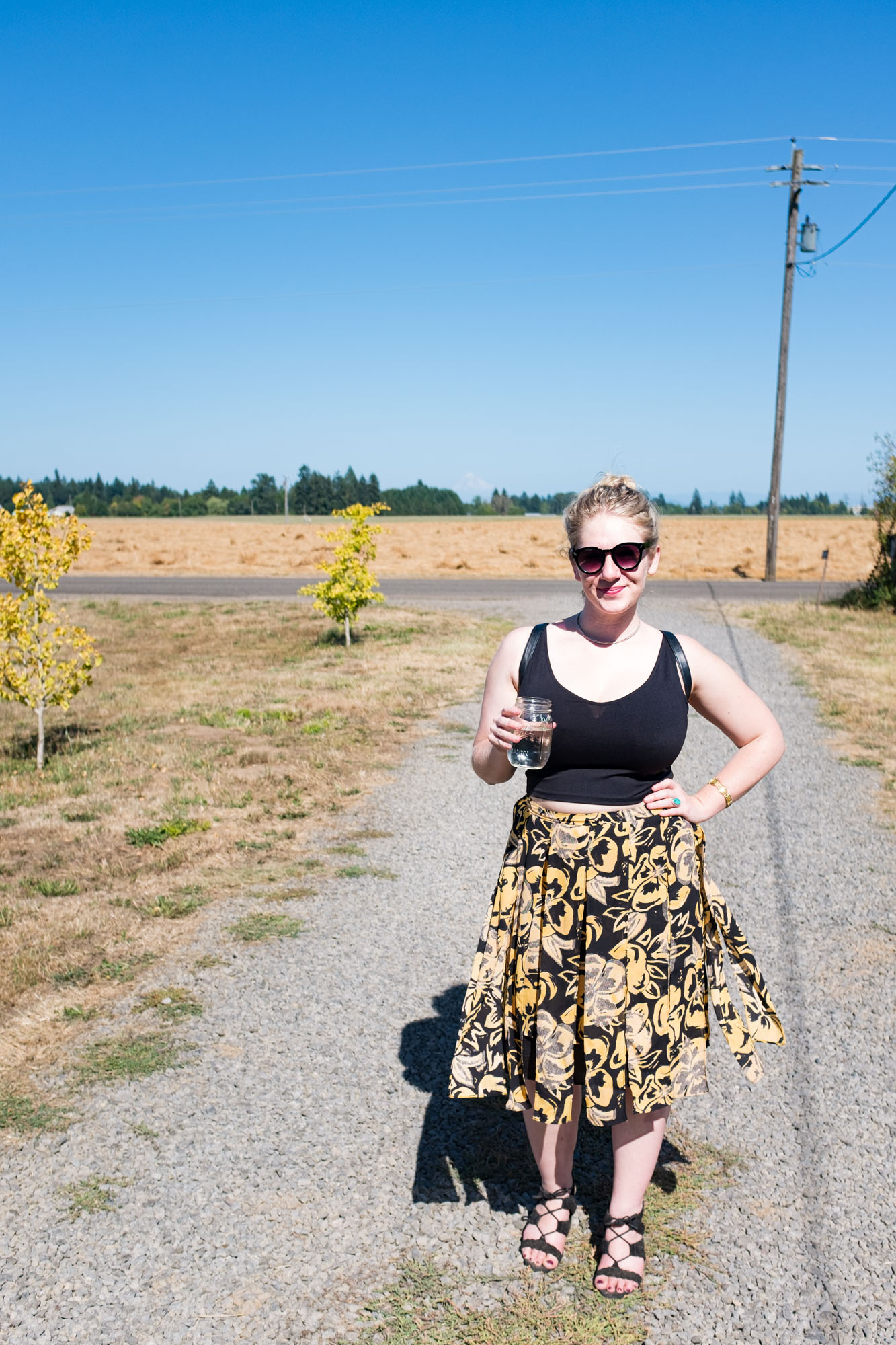 a confident lady stands in a gravel drive way holding a drink on a clear sunny day in Oregon