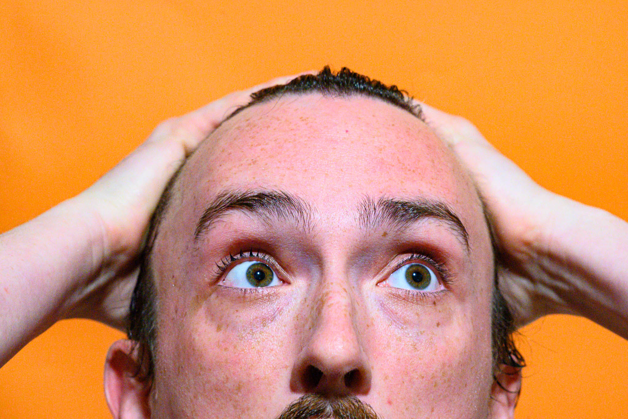 the artist runs his hands through his wet hair while standing against an orange backdrop