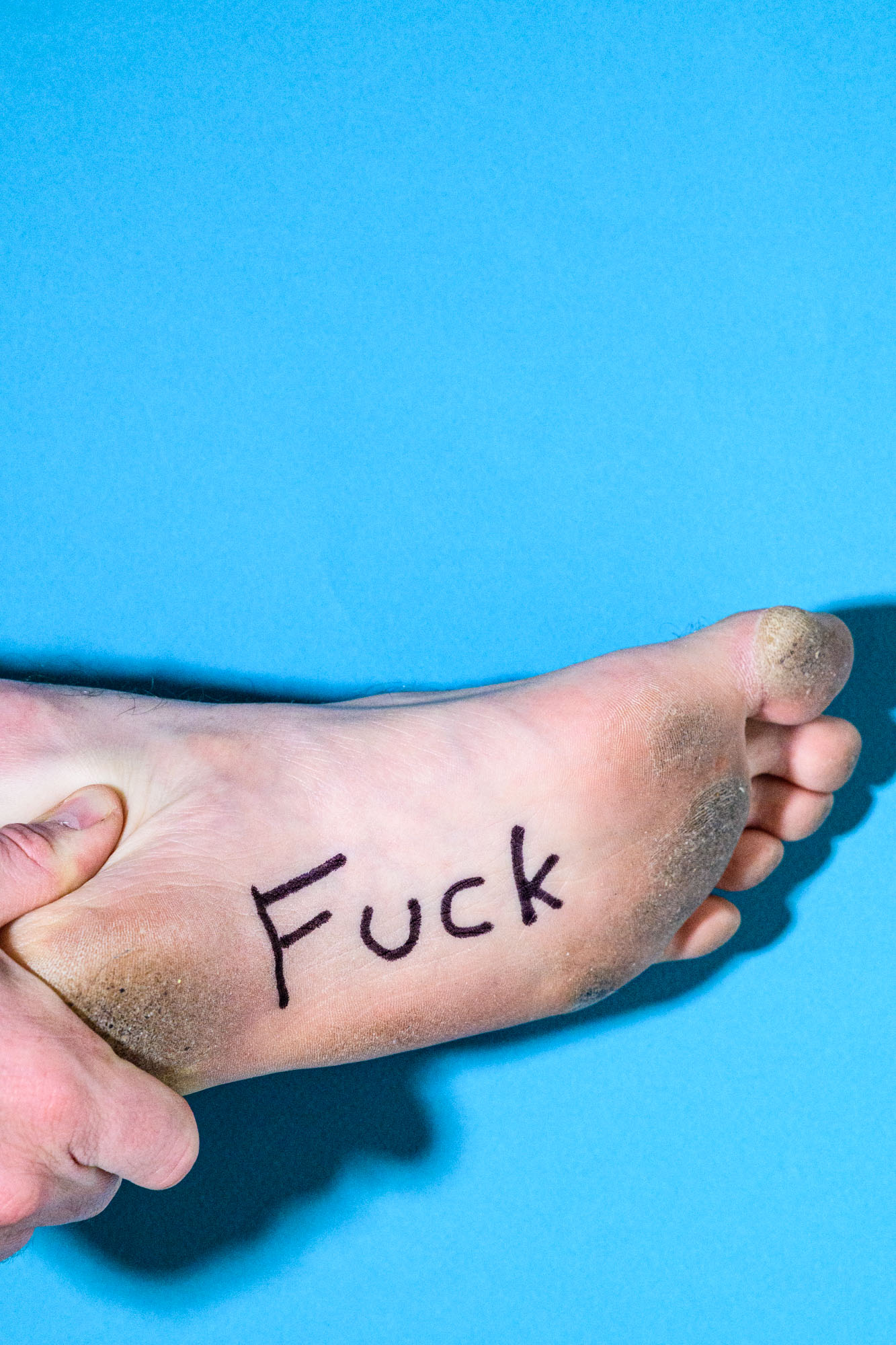 the word 'fuck' is written on the bottom of the artist's foot against a blue back drop