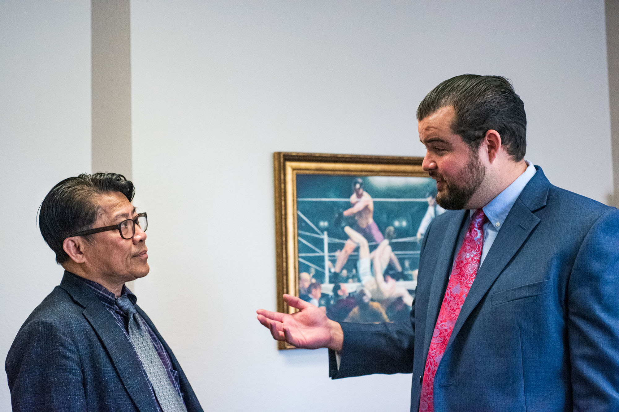 two lawyers discuss a case in front of a painting of a boxing match