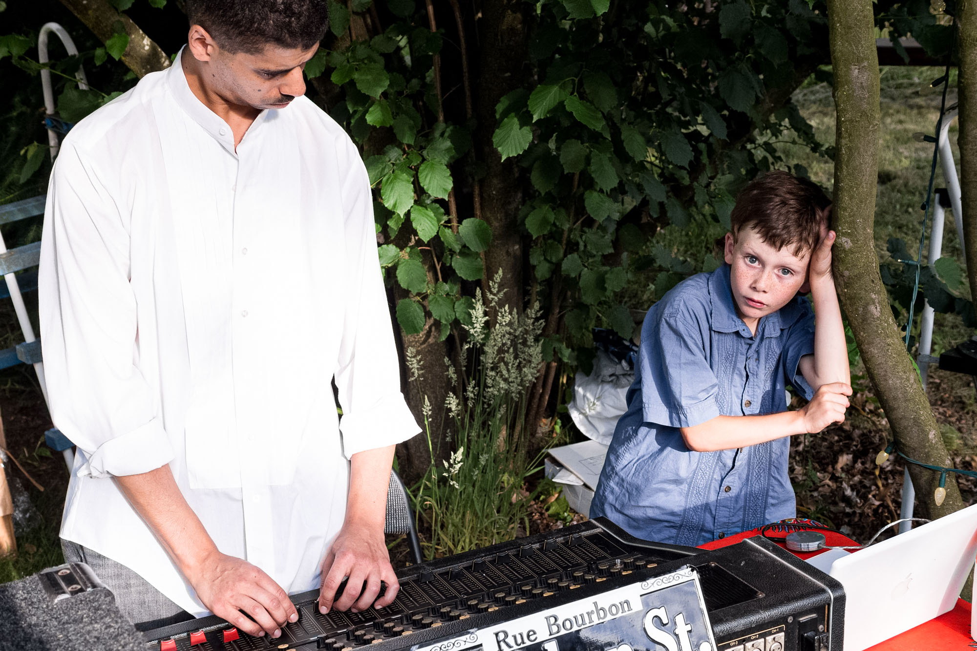 a young boy leans on a tree and eyes the camera as his dad adjusts the levels on a mixing board