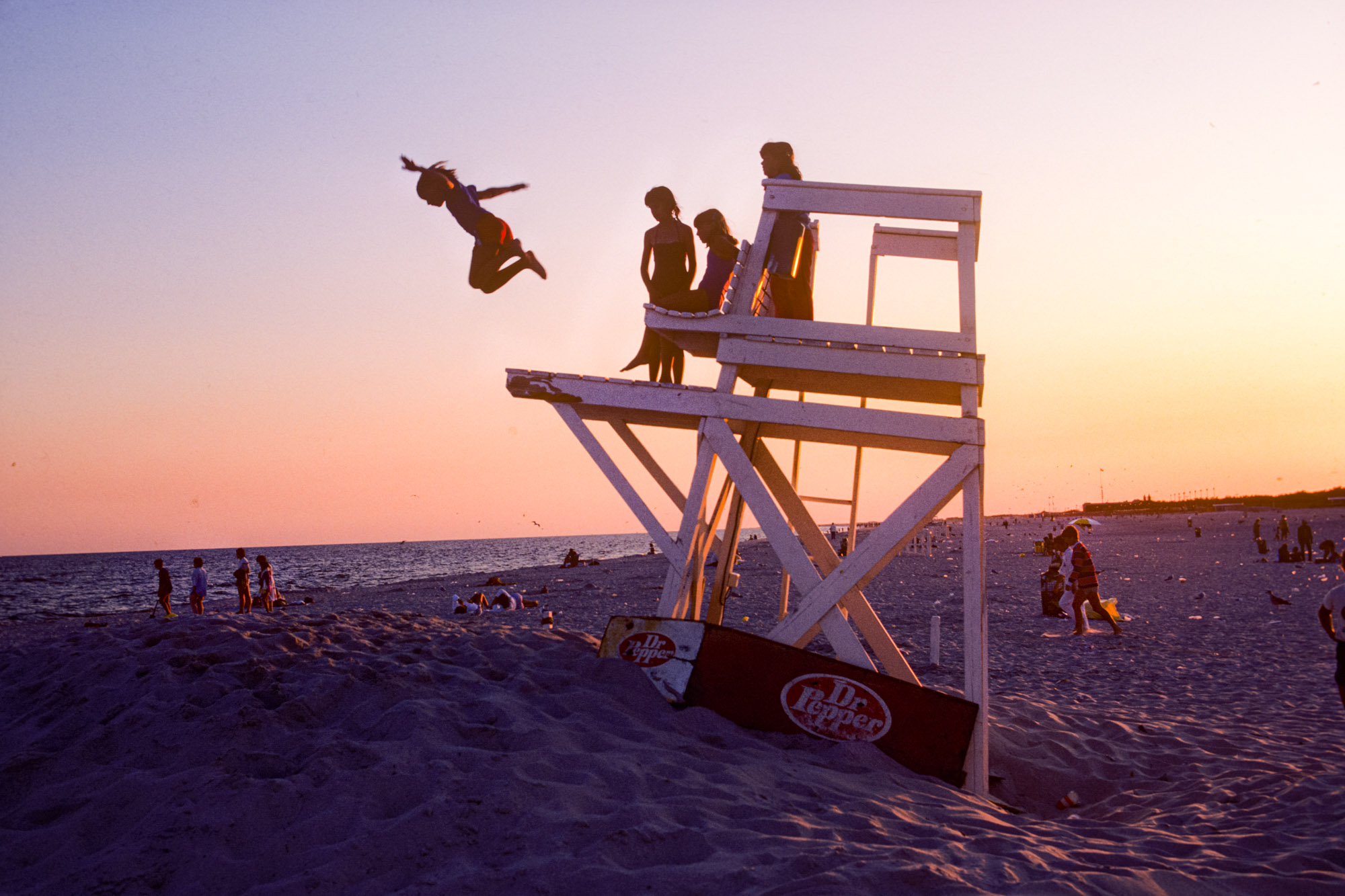 a child jumps off a lifeguard tower on a beach in New Jersey