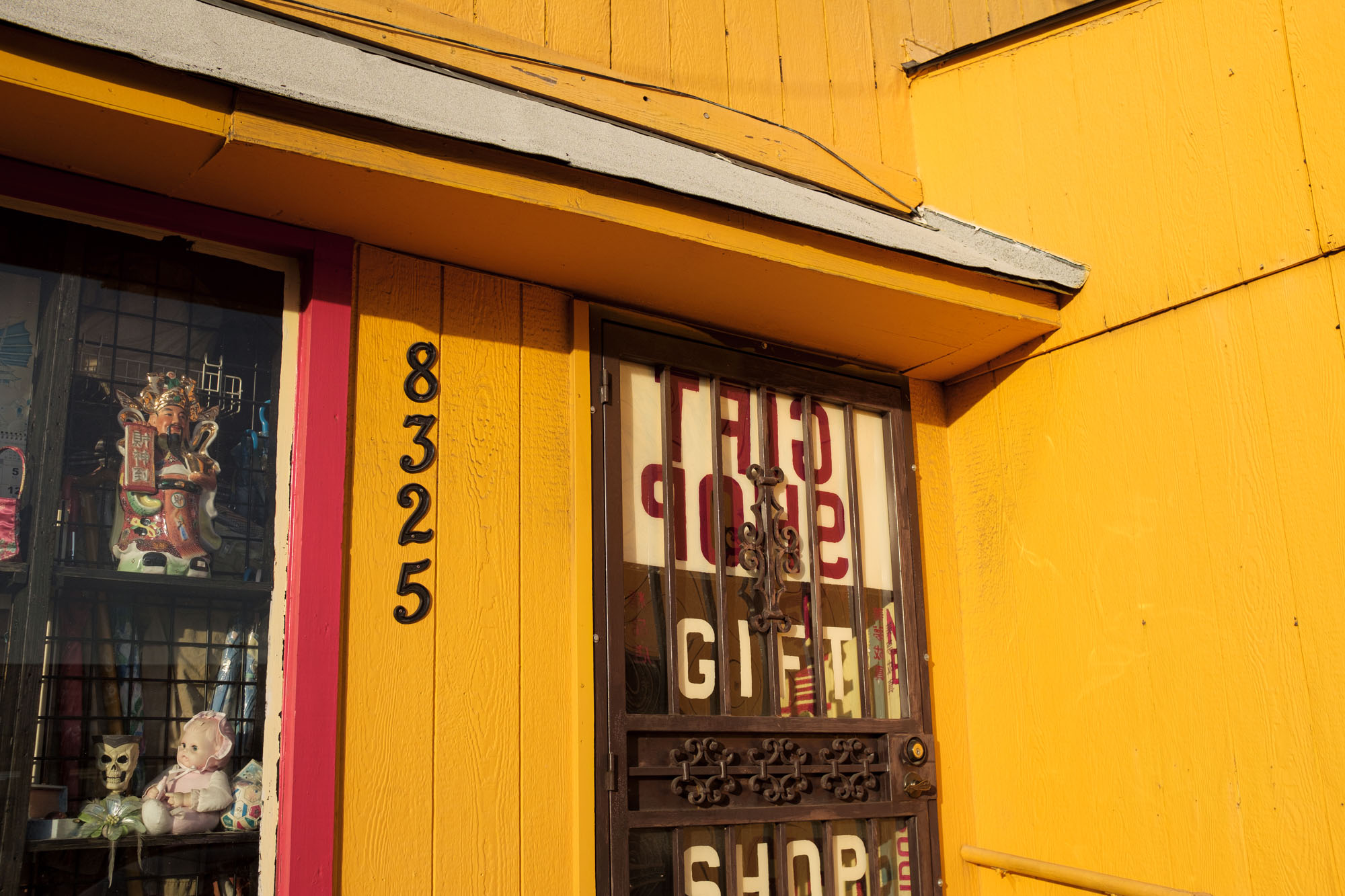 the front of a yellow building, with bars on the front door