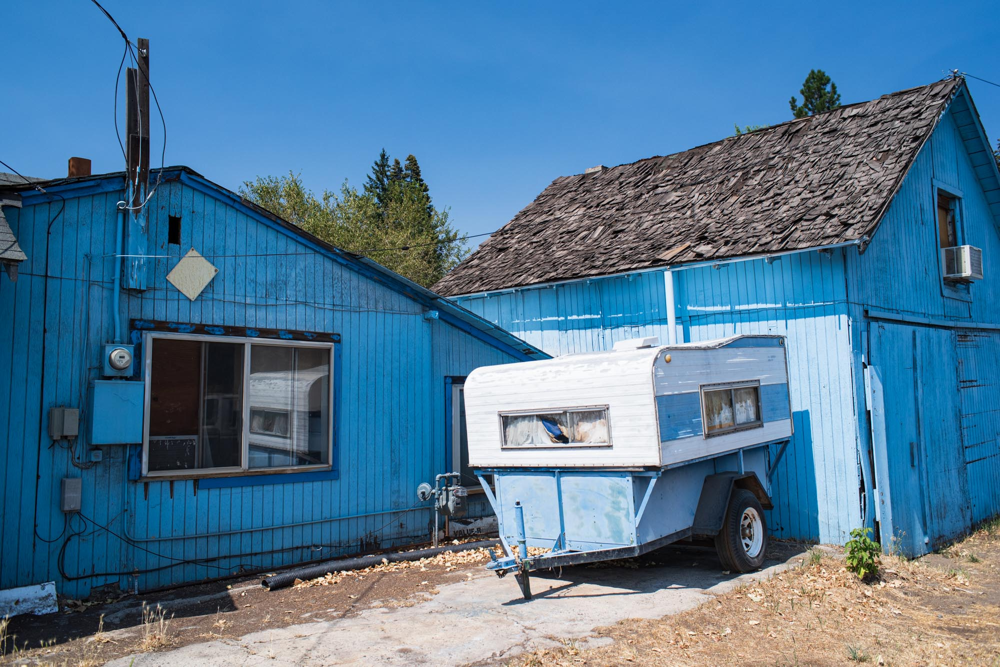a faded blue house in a small rural town with a blue and white trailer parked in front of it