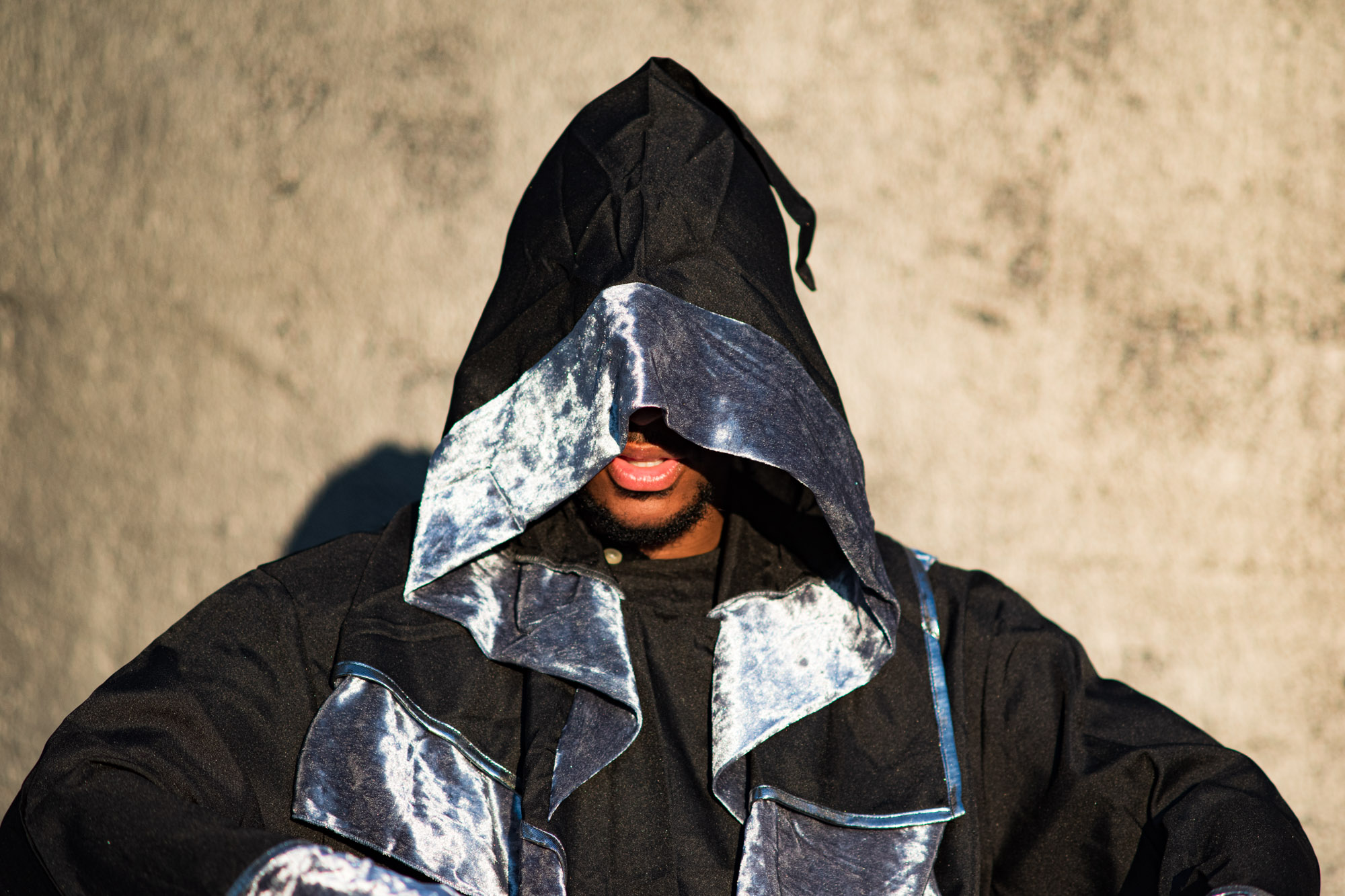 an artist wearing a shiny silver wizard suit against a stone colored backdrop