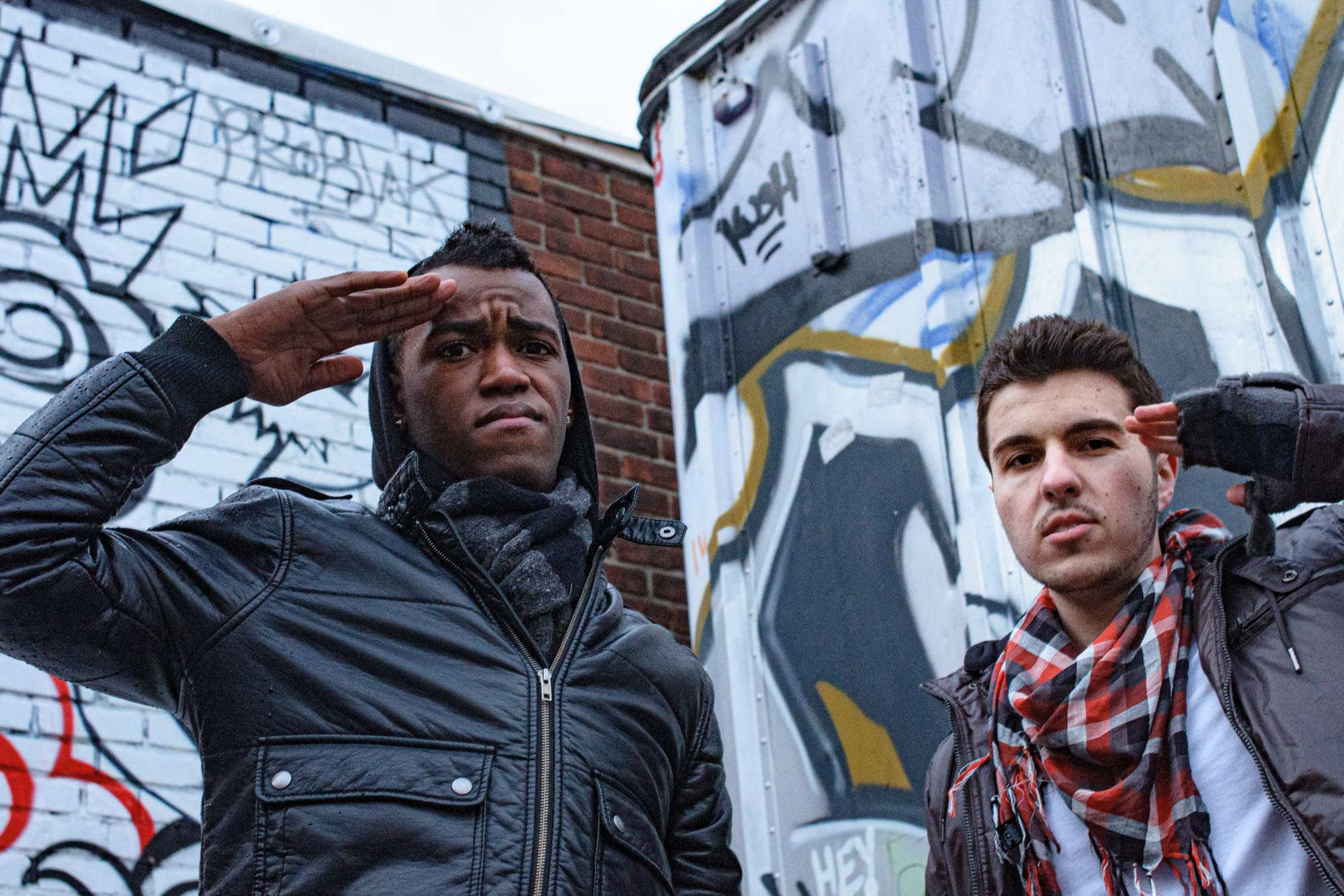 two musicians salute the camera while wearing dark leather coats and scarves