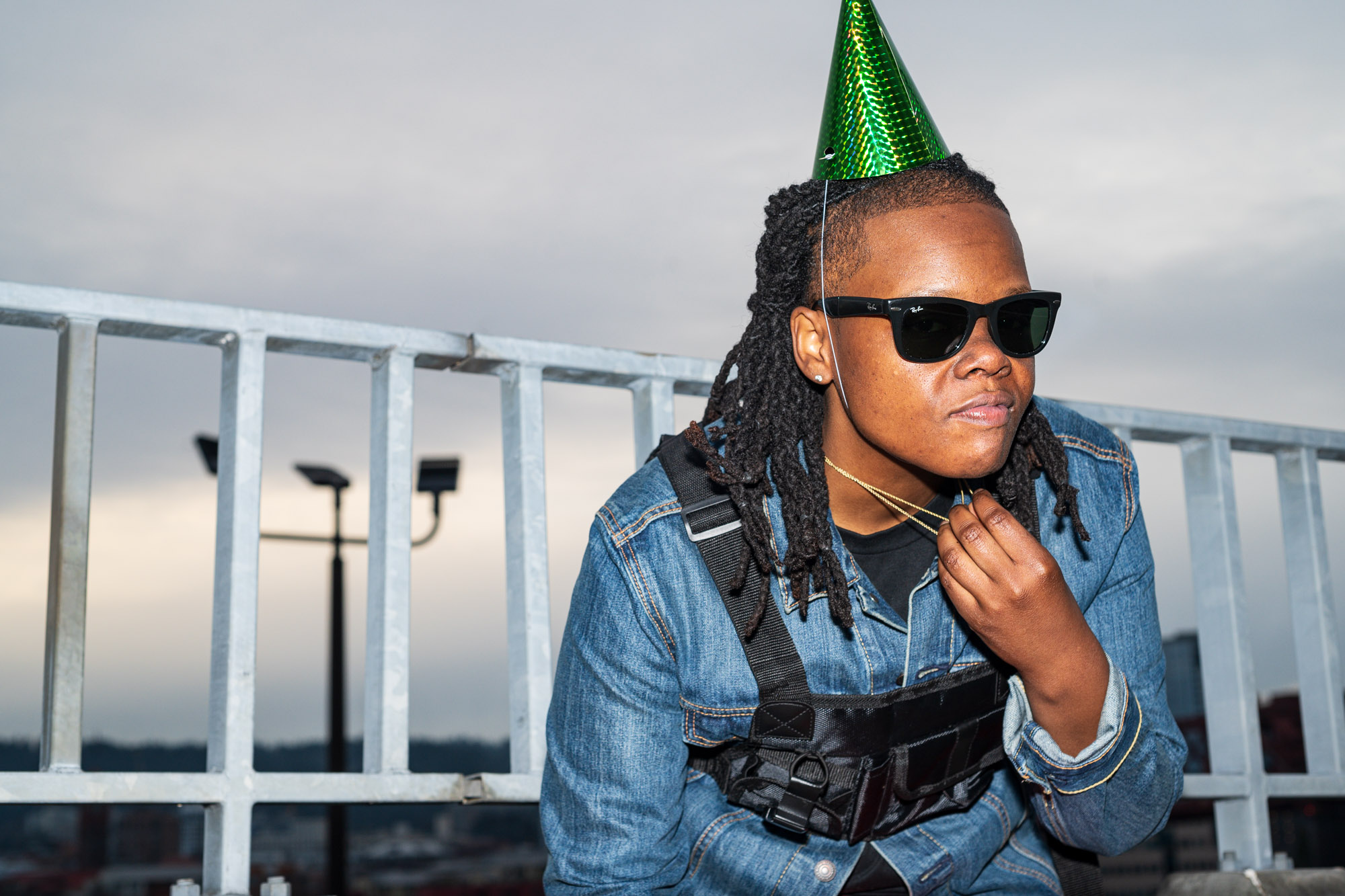 a musician poses against a silver barrier while wearing sunglasses and a green party hat