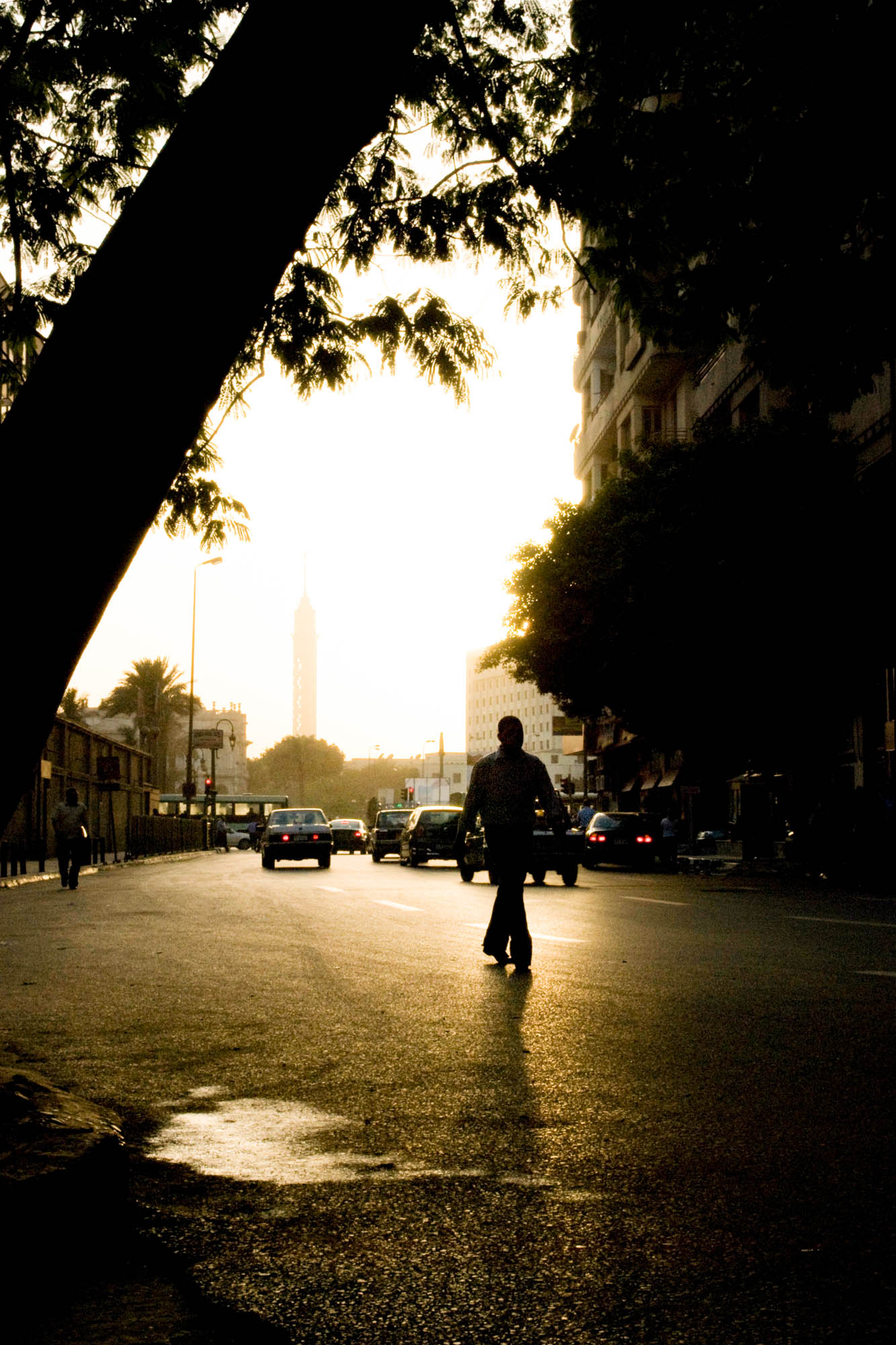 a man walks through Tahrir Square in Cairo, Egypt around dusk