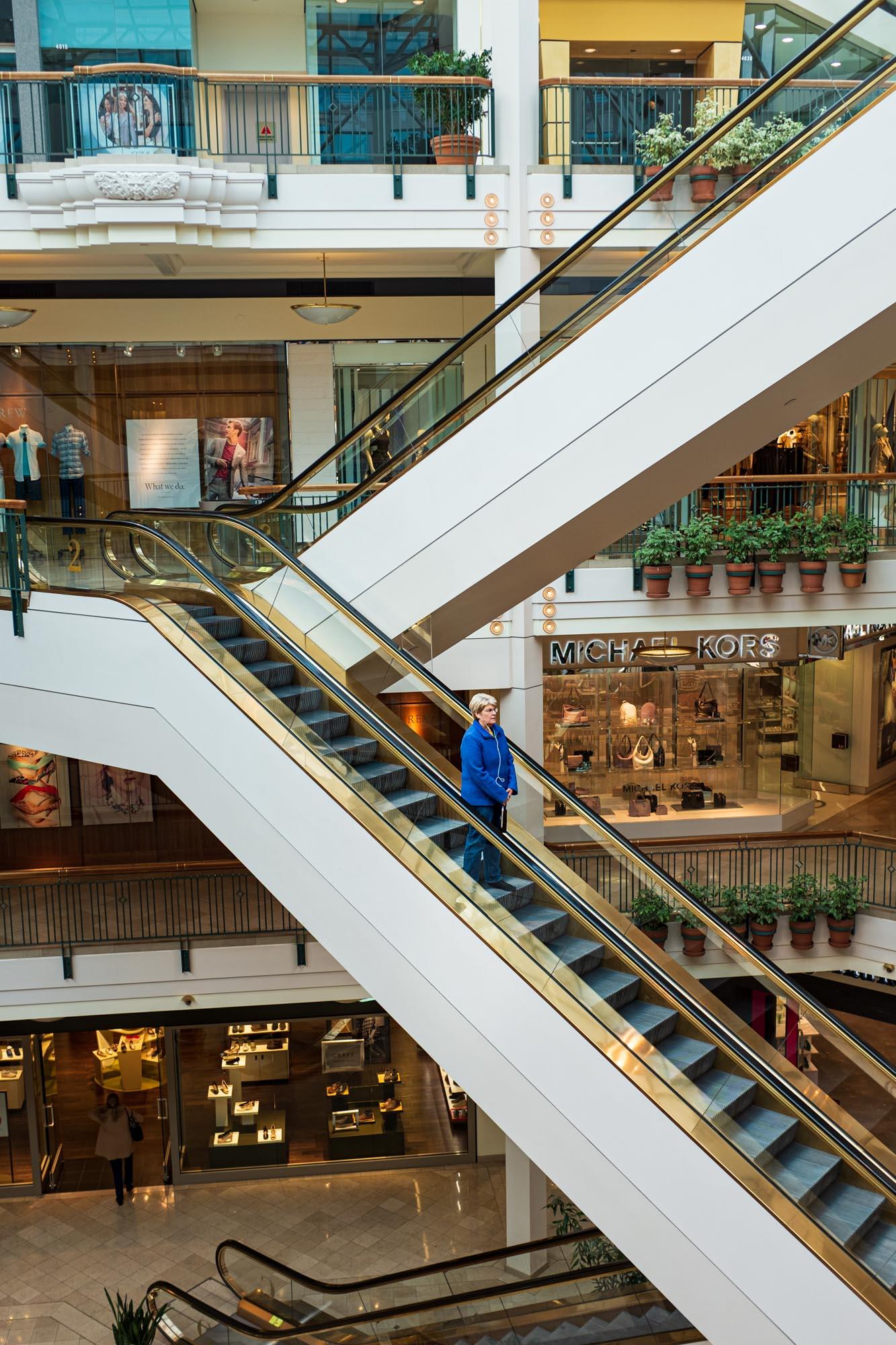 a woman descends an escalator in a mall in downtown Portland, Oregon