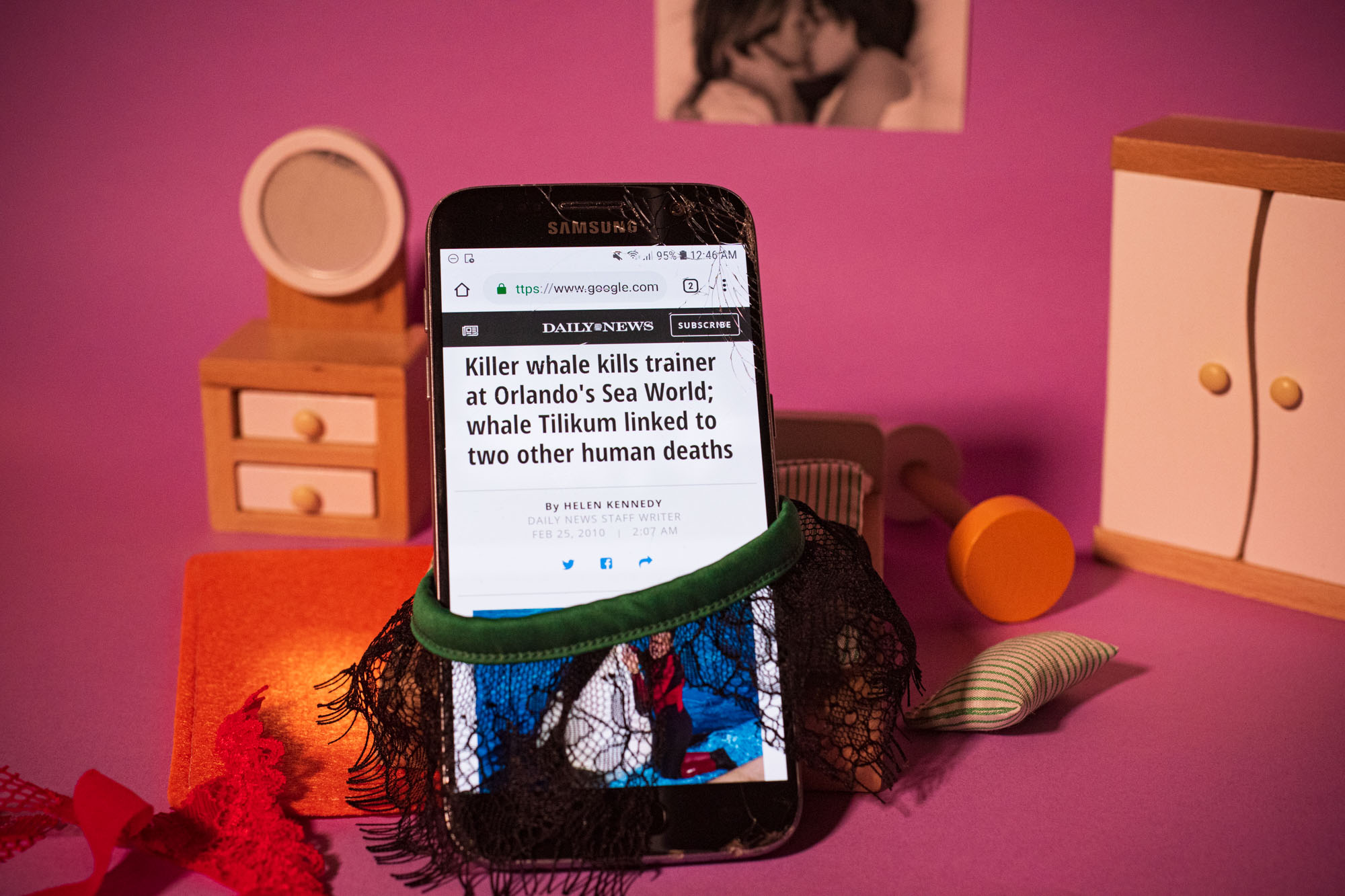 bad news is displayed on a smartphone wearing lingerie posed in a miniature bedroom set