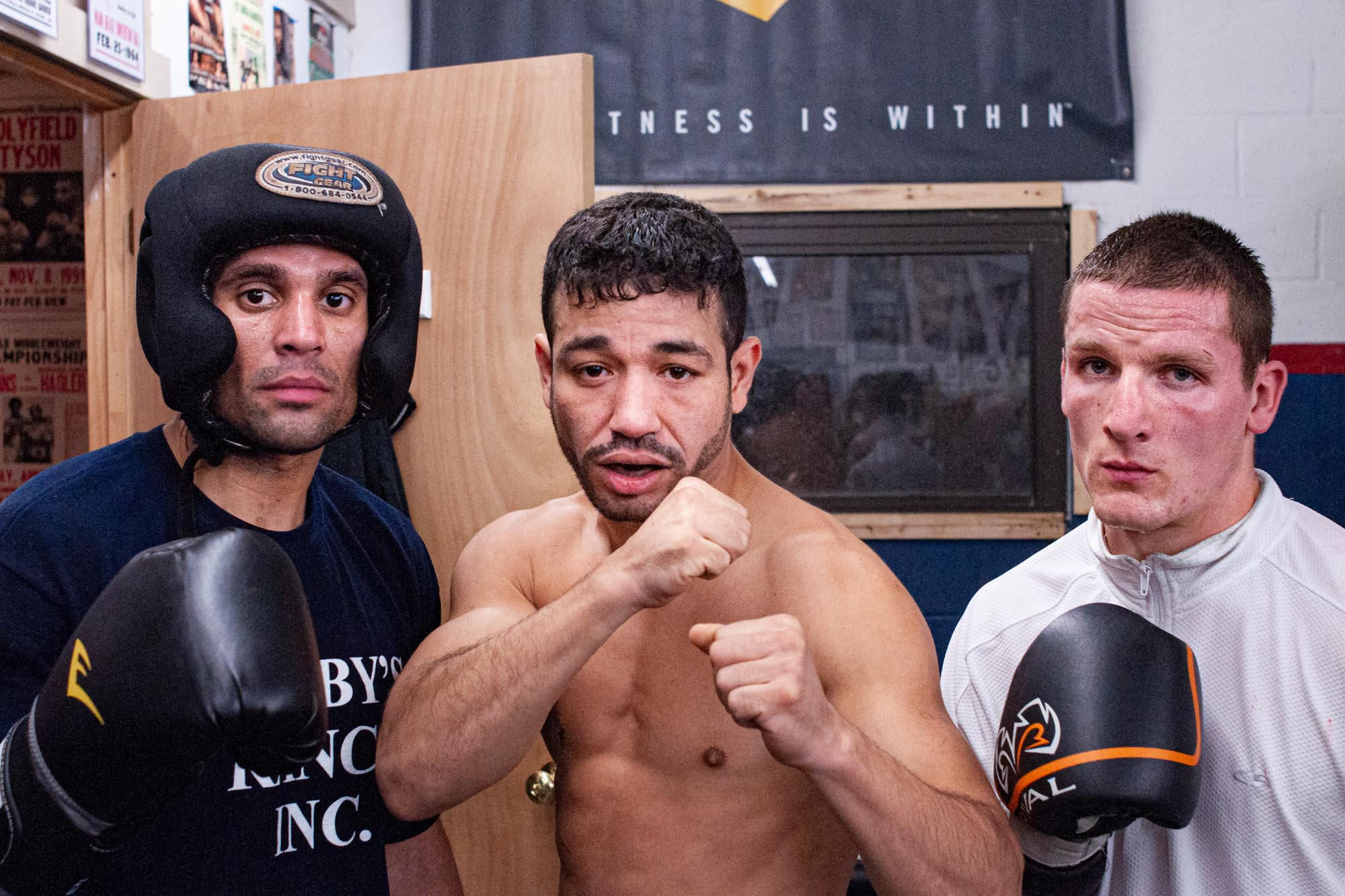 three boxers pose in the gym between sparring sessions
