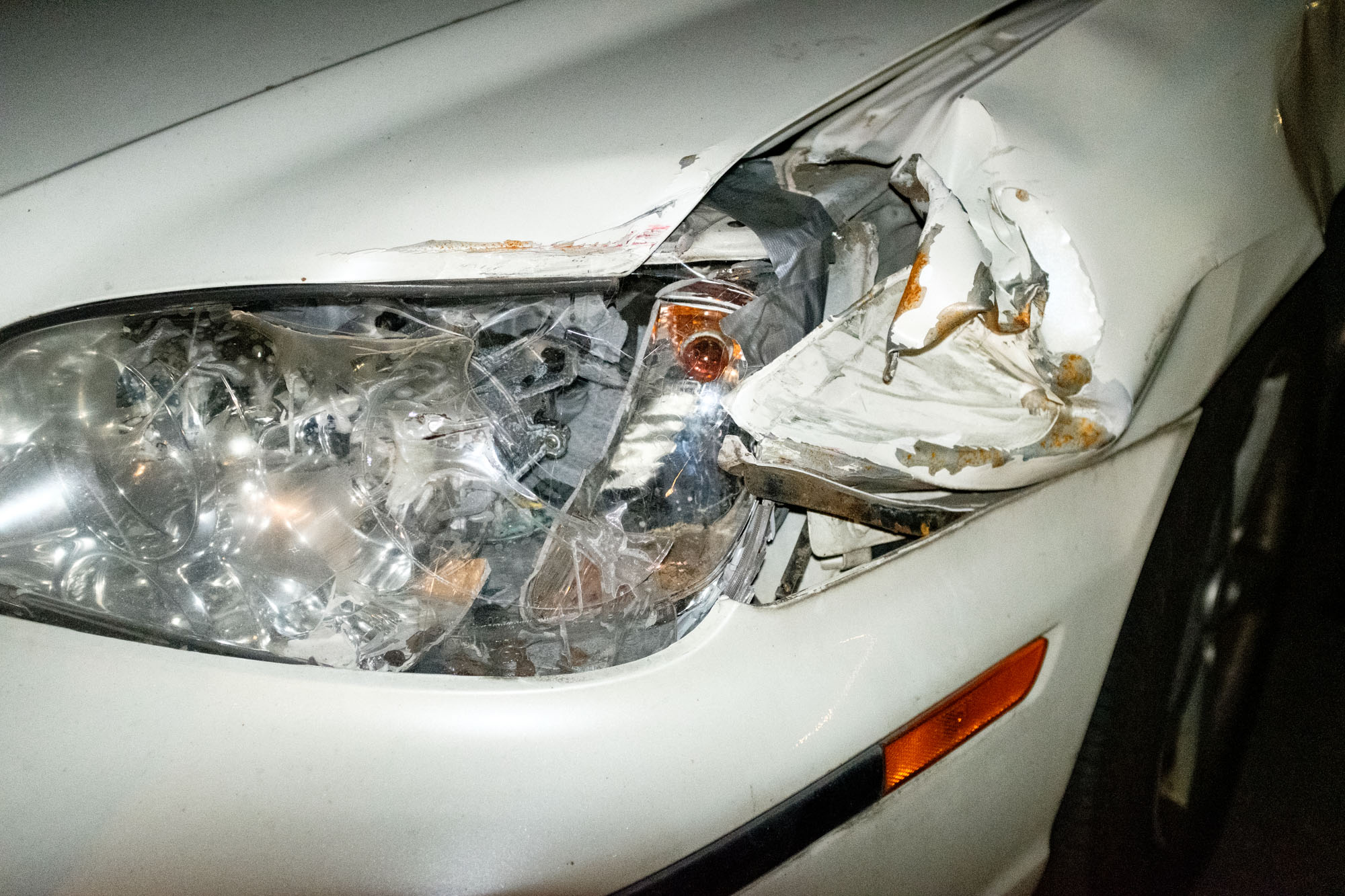 the smashed front headlight of a white sedan