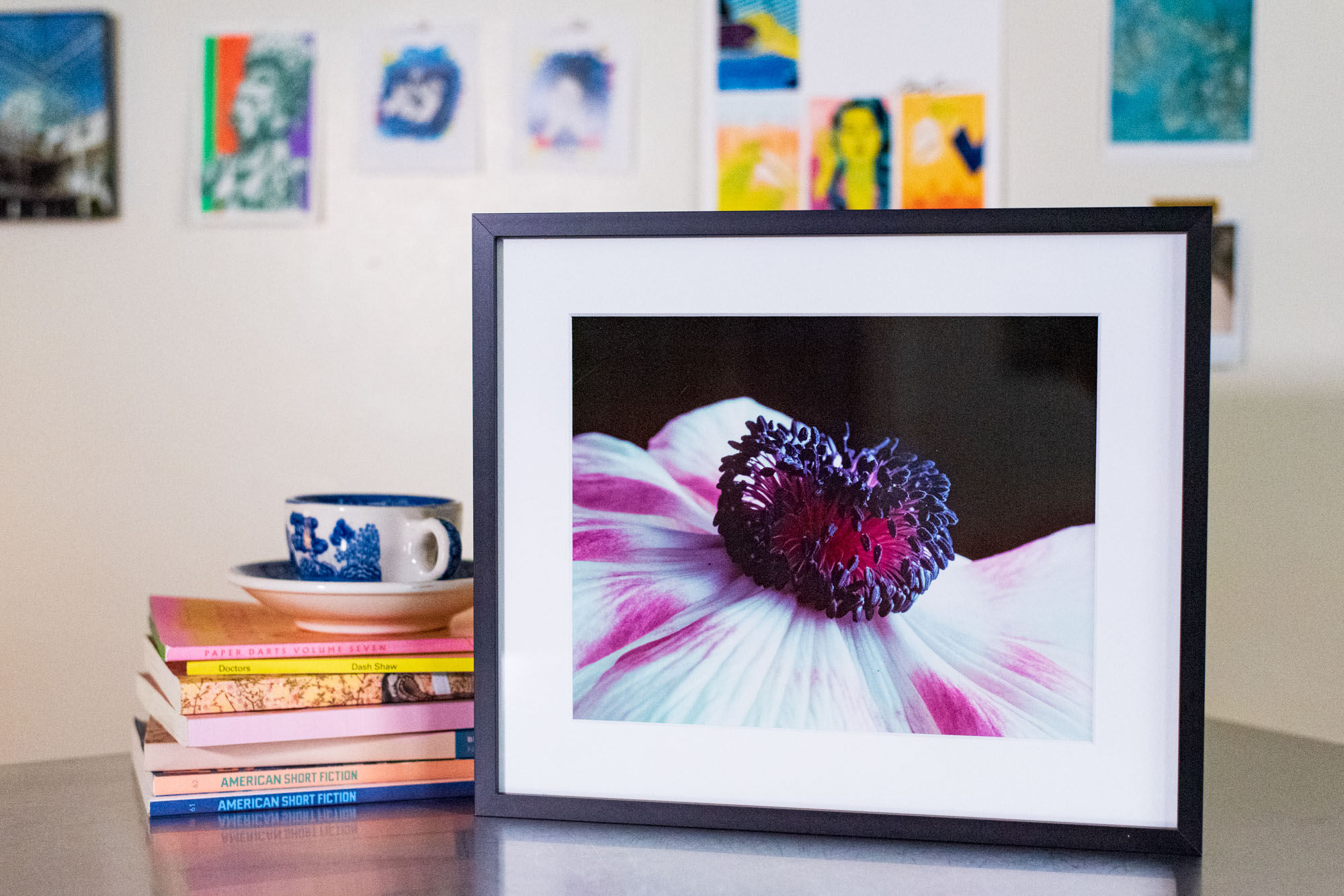 a black framed photograph of a flower posed with some books on a metal table
