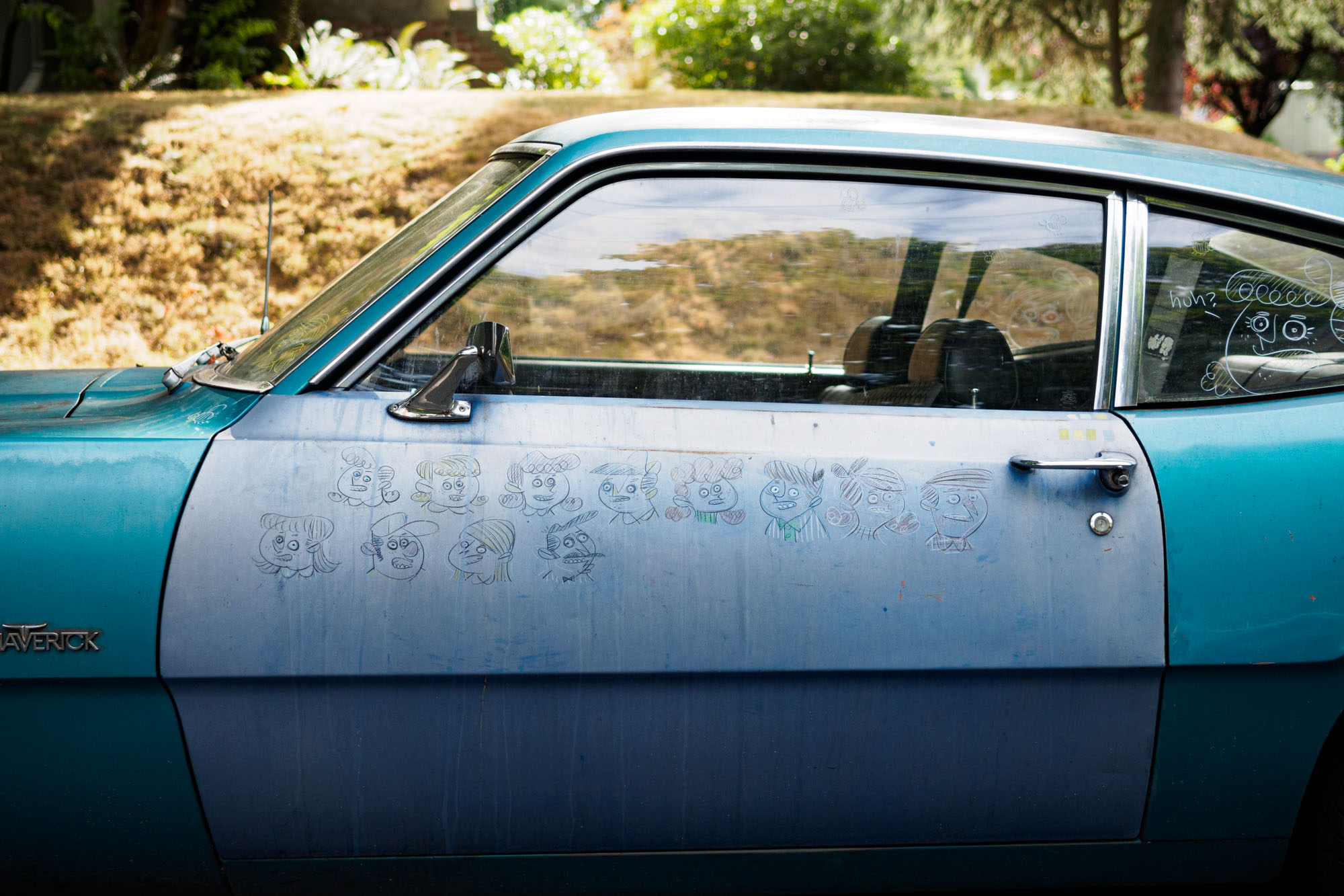 drawings on the side of an old blue car