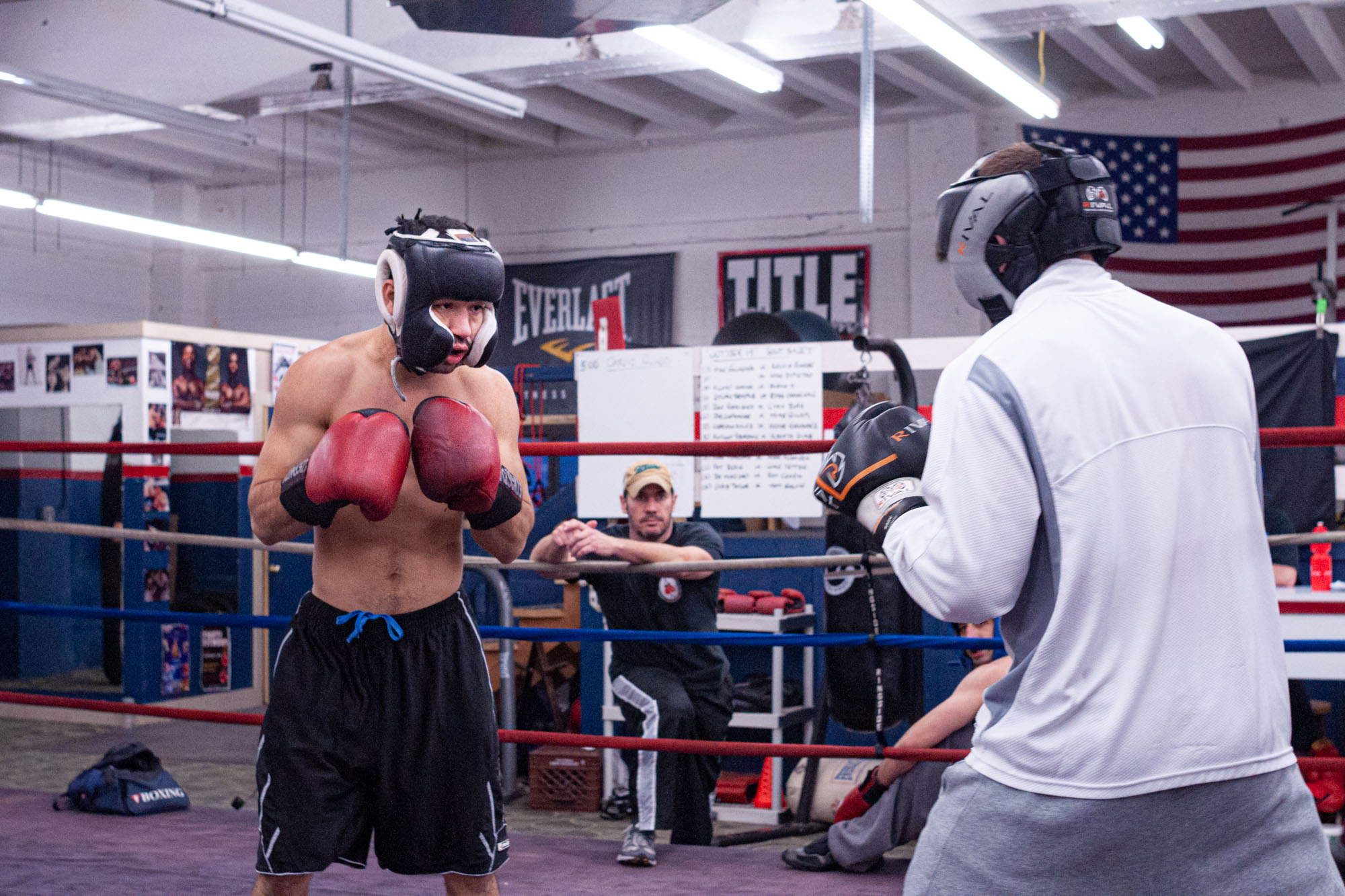 two boxers begin to spar as their coach watches between the ropes