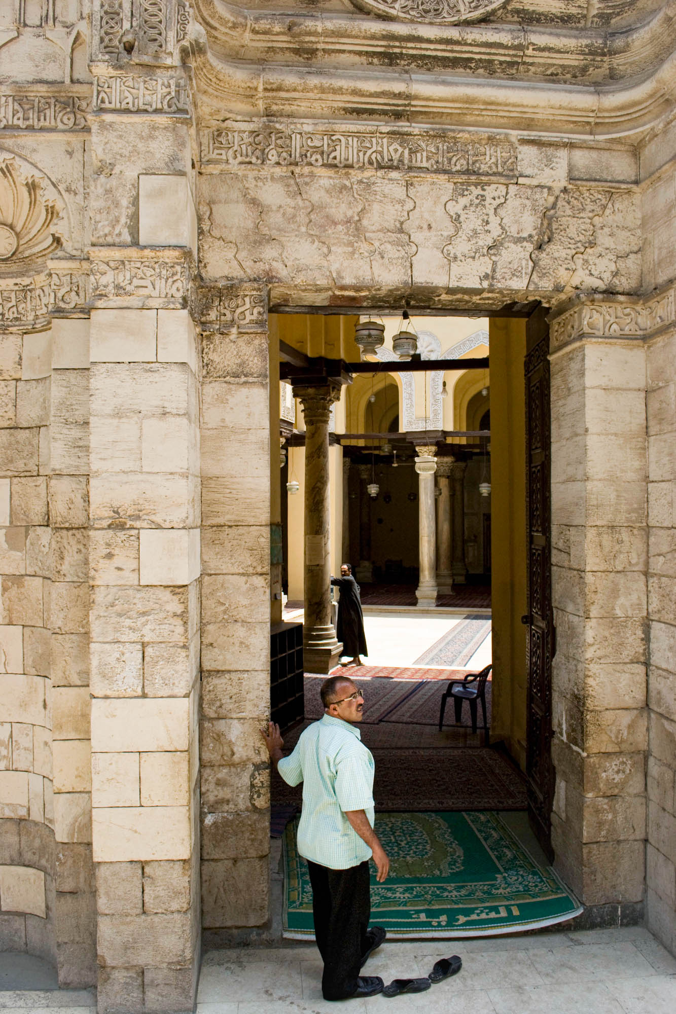 a man removes his shoes before entering a mosque to pray in Cairo, Egypt