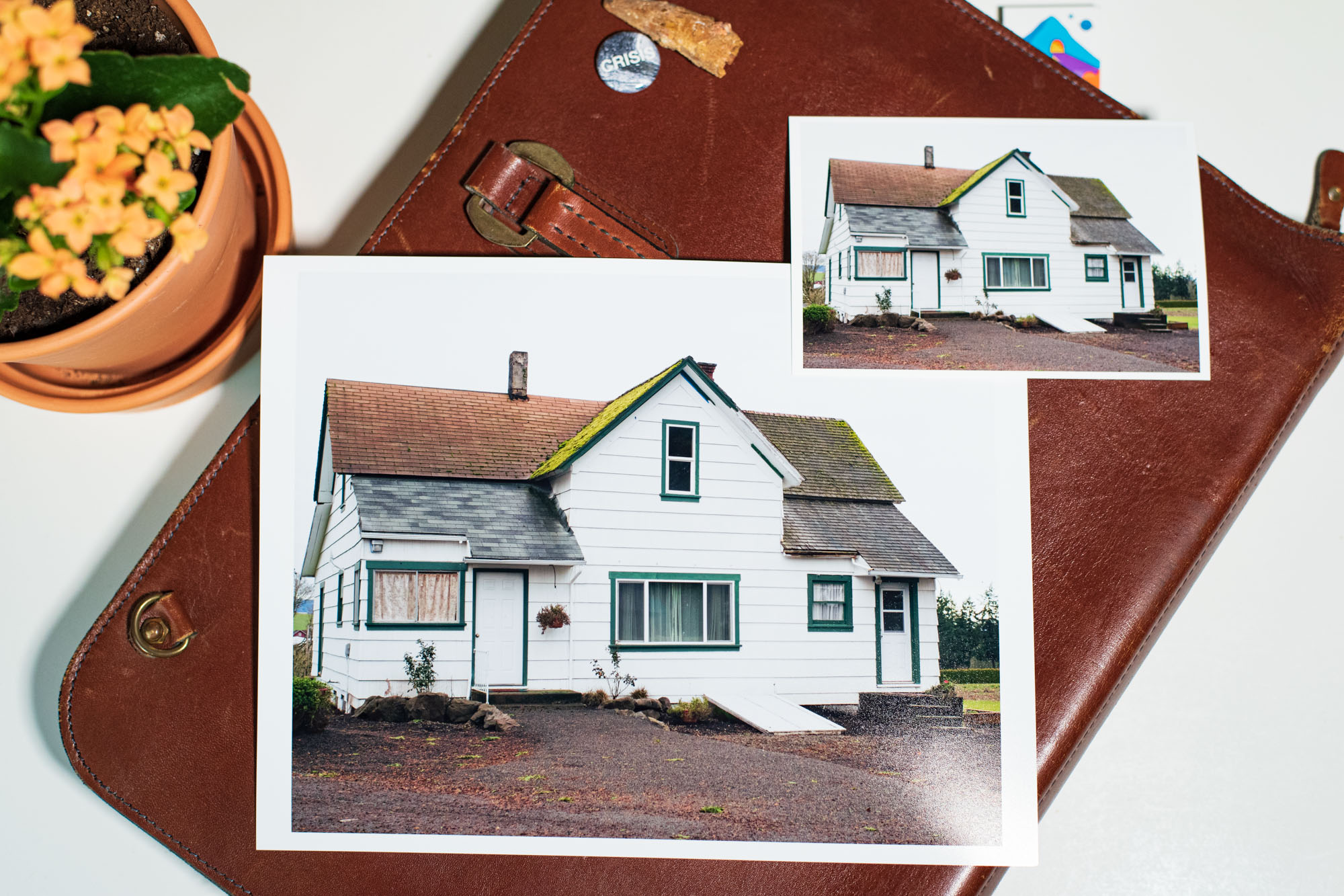 dye ink prints of a farmhouse are displayed artfully on a table