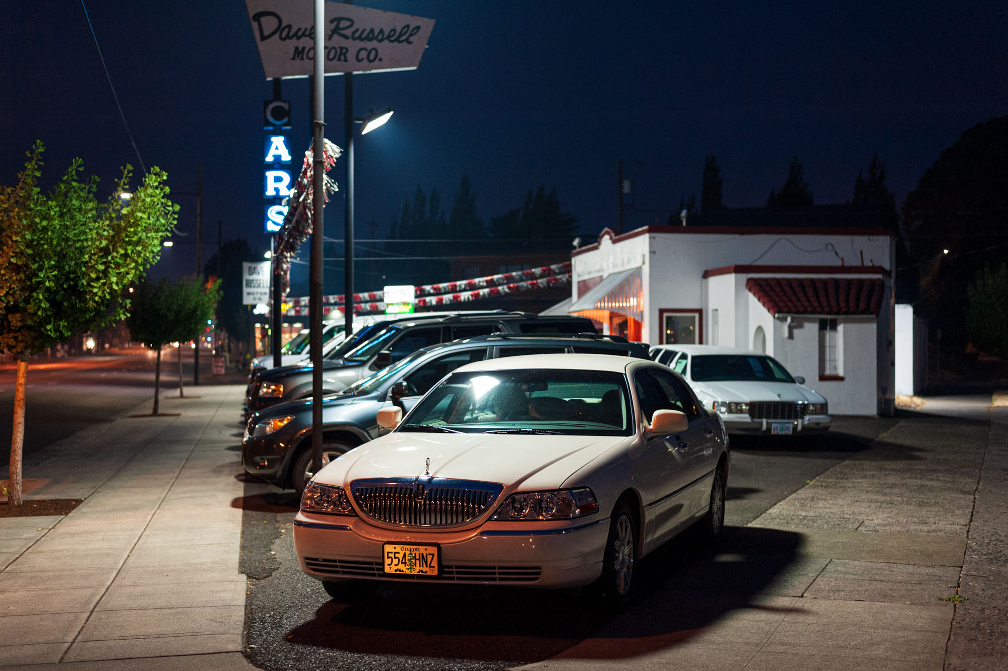 a car lot, lit brightly in the night