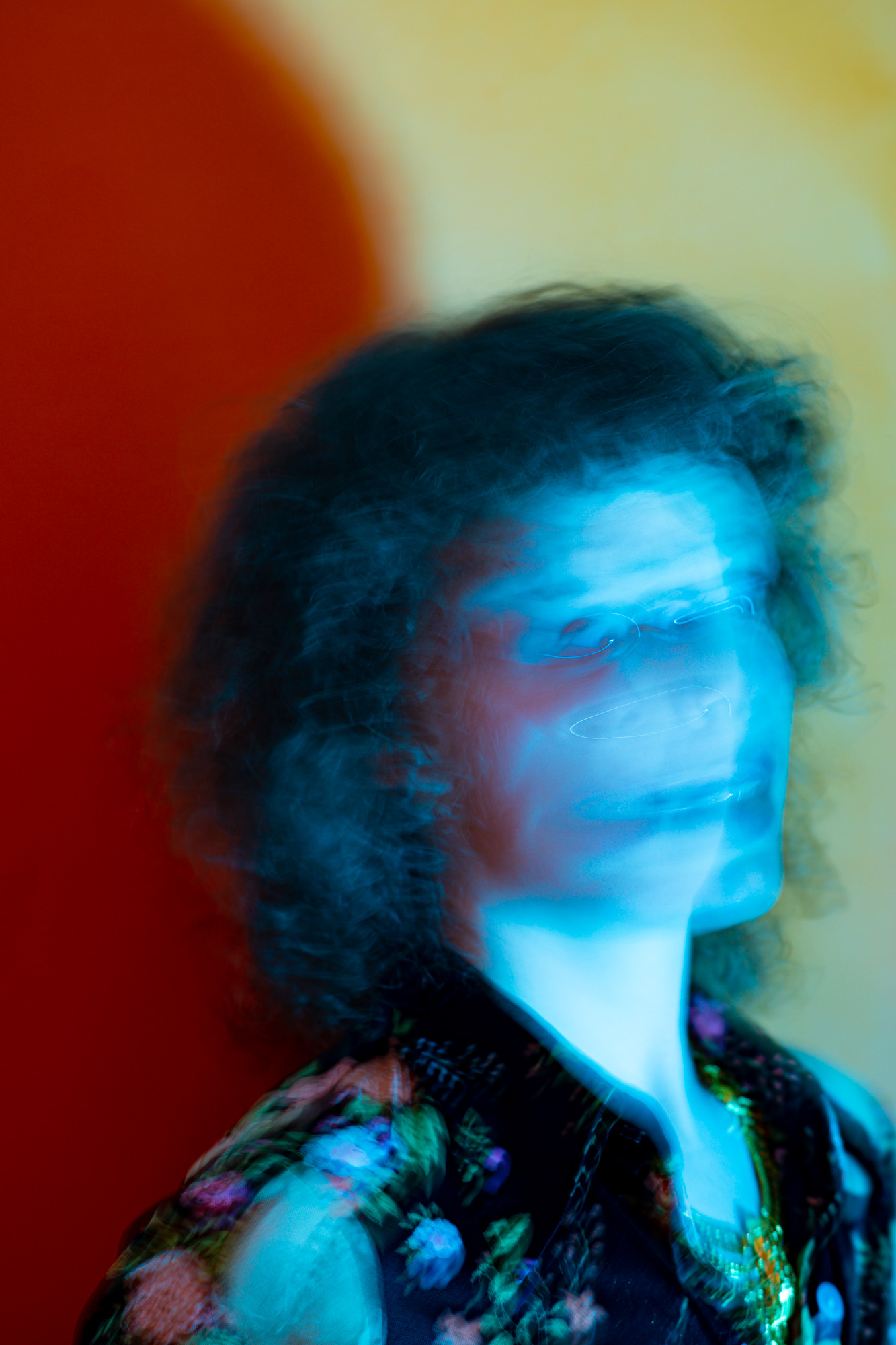 a woman yells while a bright blue light consumes the frame, blurring her face